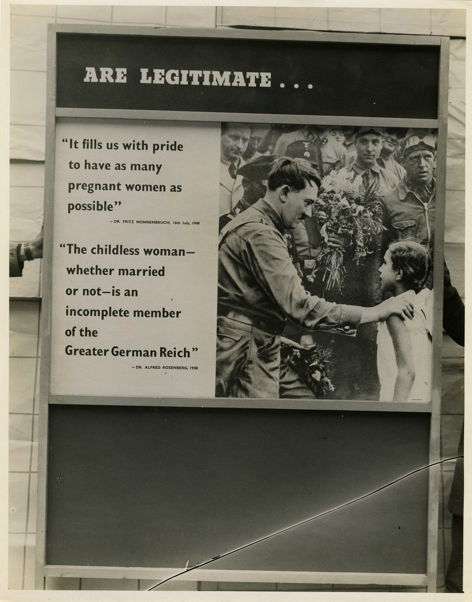 """Panel from a 1944 exhibition in London, England entitled """"Germany- the Evidence"""" showing Adolf Hitler greeting a young girl in a crowd.   The panel reads """"Are Legitimate... 'It fills us with pride to have as many pregnant women as possible' - Dr. Fritz Nonnenbruch [14th] July, 1940; 'The childless woman- whether married or not- is an incomplete member of the Greater German Reich' - Dr. Alfred Rosenberg, 1930""""   The back of the photo reads """"British Official Photograph; Distrbuted by the Ministry of Information. D. ; The Evil We Fight.; Ministry of Information Exhibition priduced by Display &Exhibitions Division for show all over Great Britain.; Display panel"""""""
