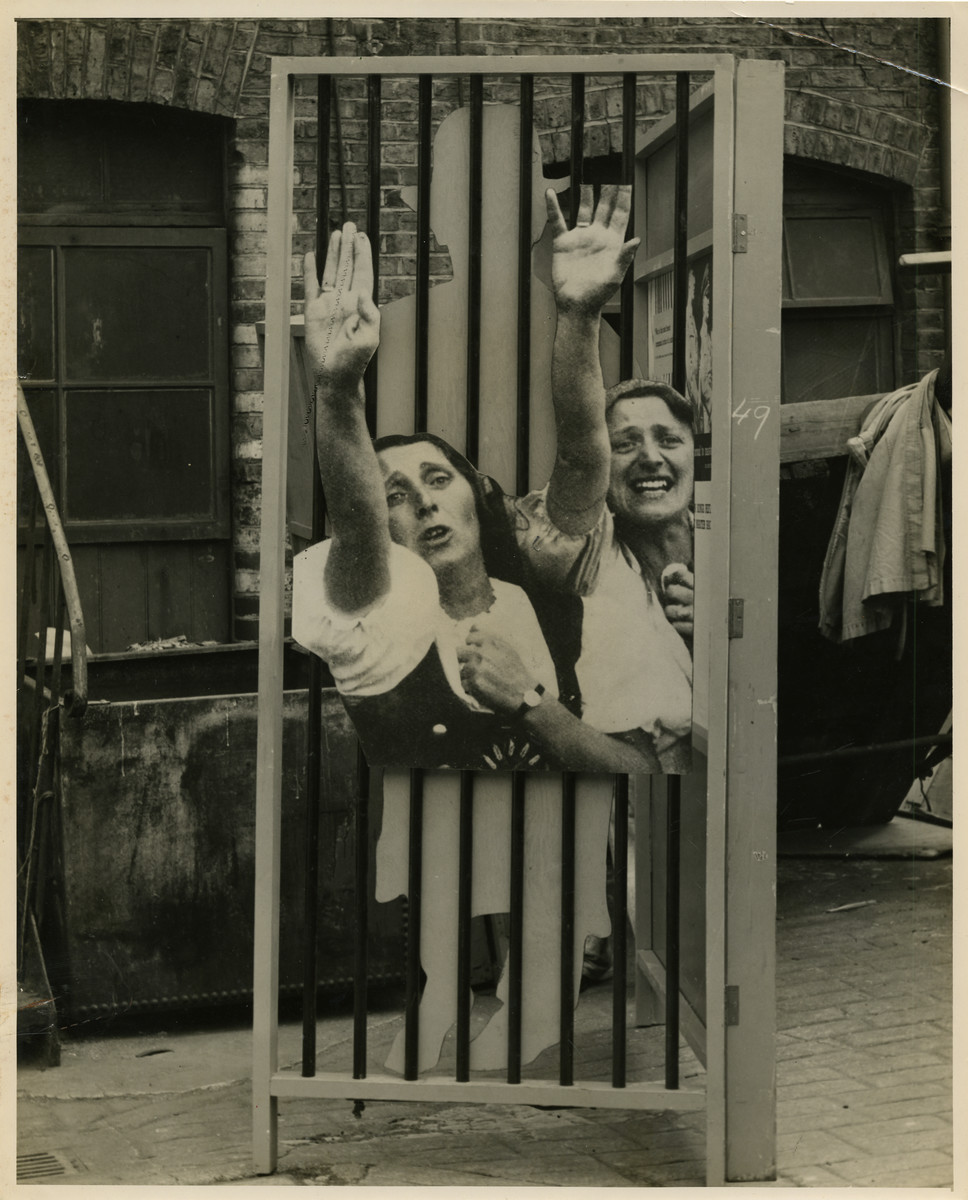 """Panel from a 1944 exhibition in London, England, entitled """"Germany- the Evidence"""" showing German women extending their right arm in the Hitler salute.    Panel shows presumably German women zealously extending their right arm in the Hitler salute dressed in traditional dirndl skirts.   The back of the photo reads """"British Official Photograph; Distrbuted by the Ministry of Information. D. ; The Evil We Fight.; Ministry of Information Exhibition priduced by Display &Exhibitions Division for show all over Great Britain.; Display panel"""""""