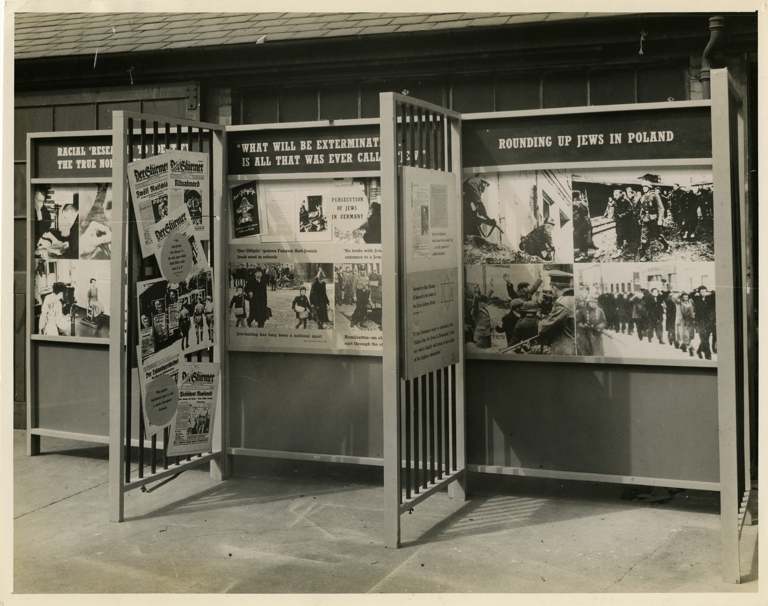 """Panel from a 1944 exhibition in London, England, entitled """"Germany- the Evidence"""" showing German antisemitism and persecution against the Jews.   The panels are titled """"Racial 'Research' To Identify the True Nordic [Race]"""", """"What Will Be Exterminated Is All That Was Called [A] Jew"""", and """"Rounding Up Jews in Poland"""" and describe the antisemitic measures that the Nazi Regime implemented during World War II.   The back of the photo reads """"British Official Photograph; Distrbuted by the Ministry of Information. D. ; The Evil We Fight.; Ministry of Information Exhibition priduced by Display &Exhibitions Division for show all over Great Britain.; Display panel"""""""
