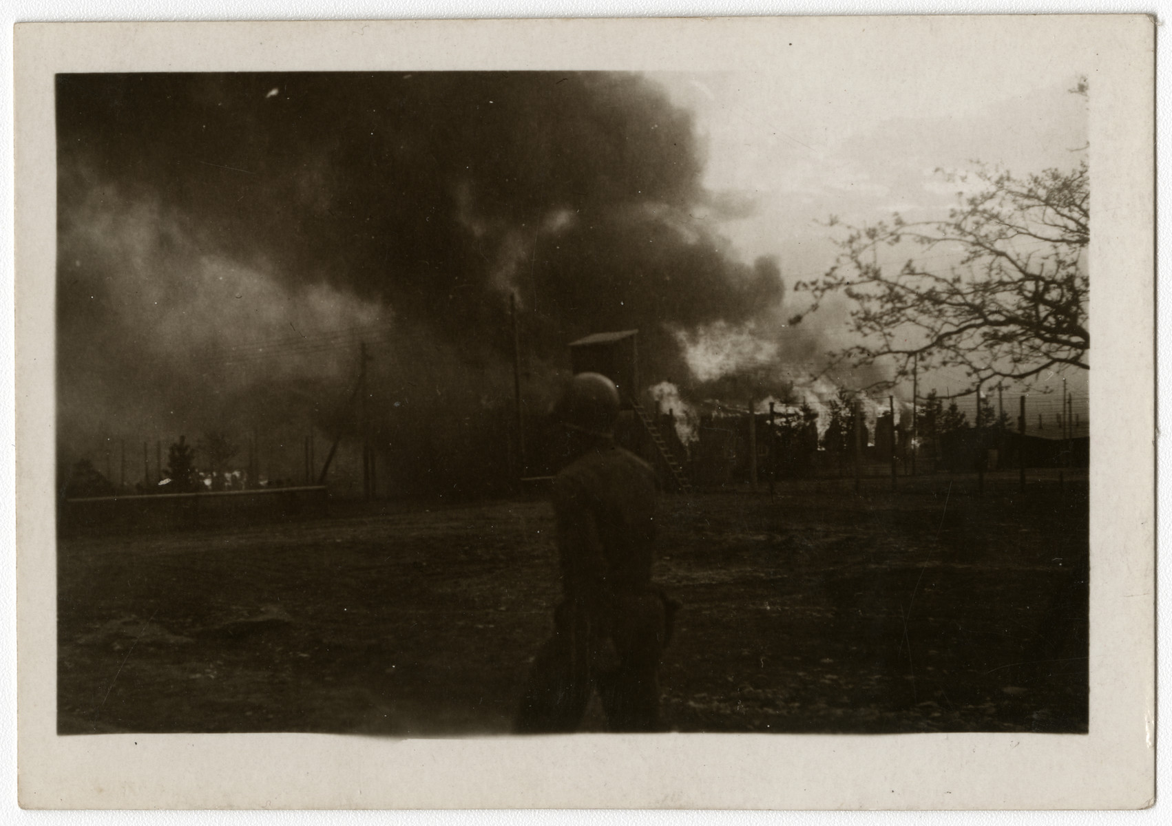 An American soldier walks past a fire burning in the Ohrdruf concentration camp.  The original caption reads: Ohrdruff concentration camp, fire again.""