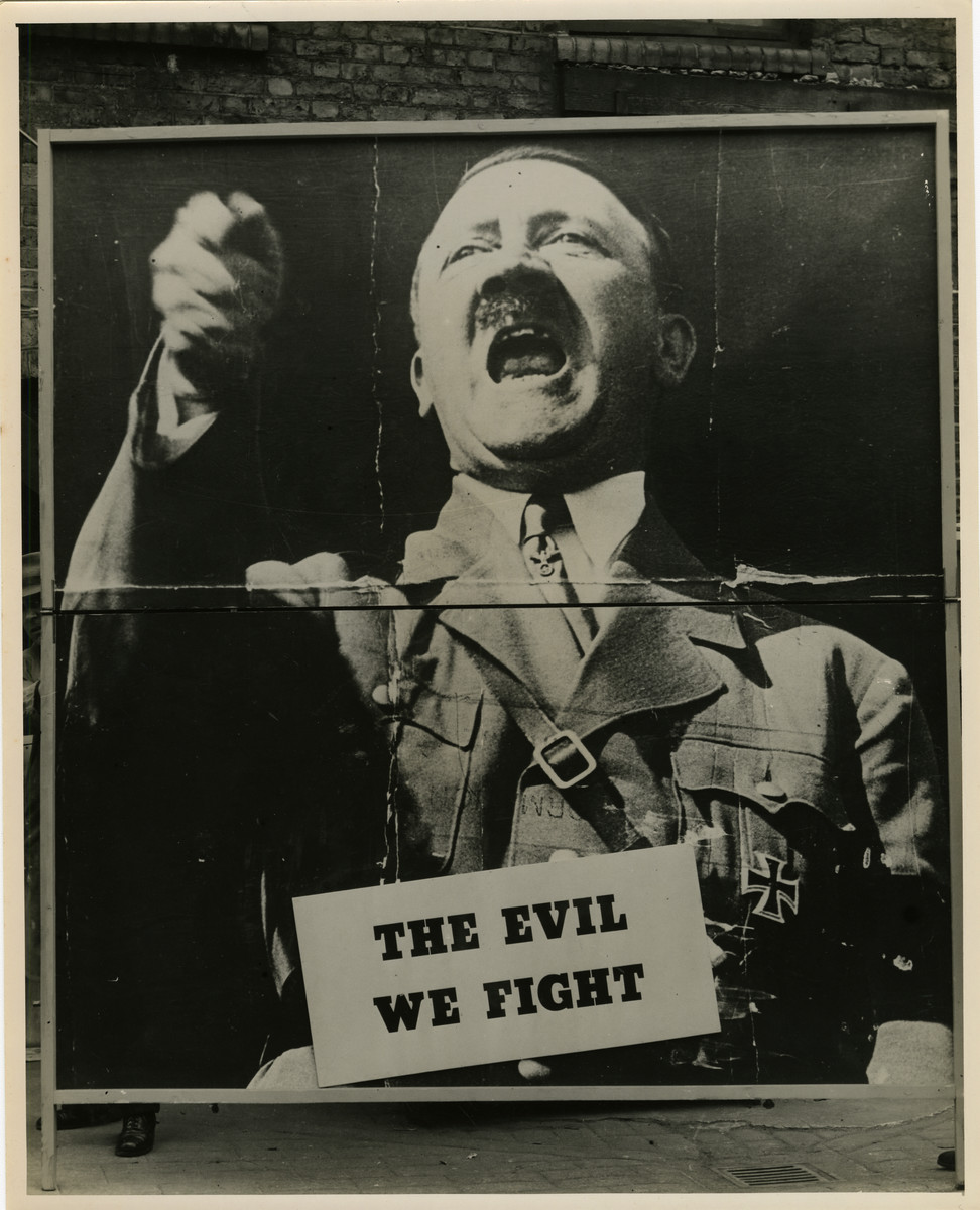 "Panel from a 1944 exhibition in London, England, entitled ""Germany- the Evidence"" showing Adolf Hitler.   The exhibit panel reads ""The Evil We Fight.""  The back of the photo reads ""British Official Photograph; Distrbuted by the Ministry of Information. D. ; The Evil We Fight.; Ministry of Information Exhibition priduced by Display & Exhibitions Division for show all over Great Britain.; Display panel"""