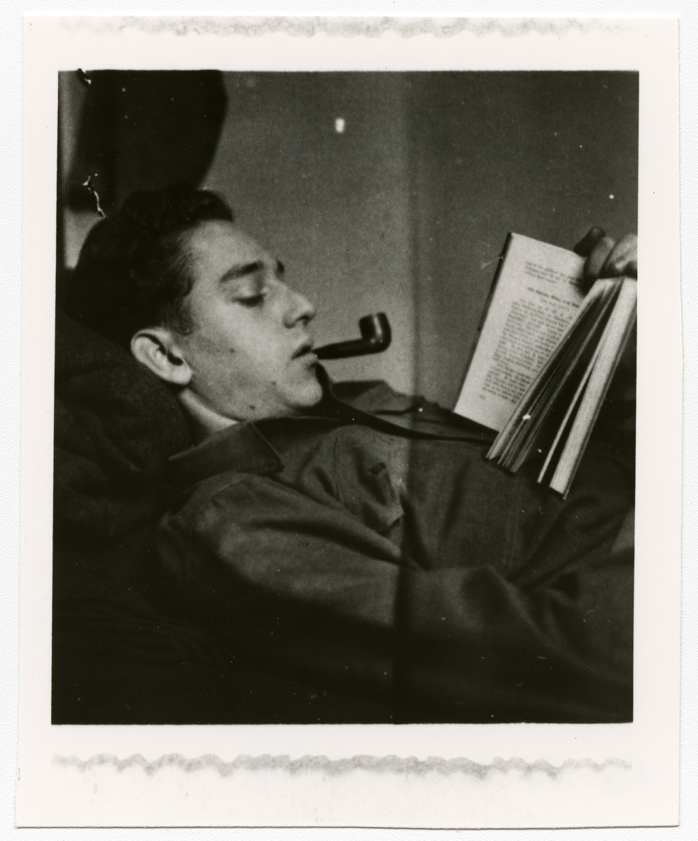 American GI Lee Merel relaxes by reading and smoking a pipe.