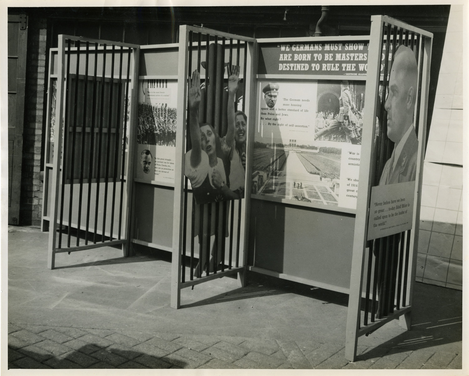 "Panel from a 1944 exhibition in London, England, entitled ""Germany- the Evidence.""   Quote from the panel reads ""We Germans must show that we are born to be masters [and are] destined to rule the world.""   The back of the photo reads ""British Official Photograph; Distrbuted by the Ministry of Information. D. ; The Evil We Fight.; Ministry of Information Exhibition priduced by Display & Exhibitions Division for show all over Great Britain.; Display panel"""