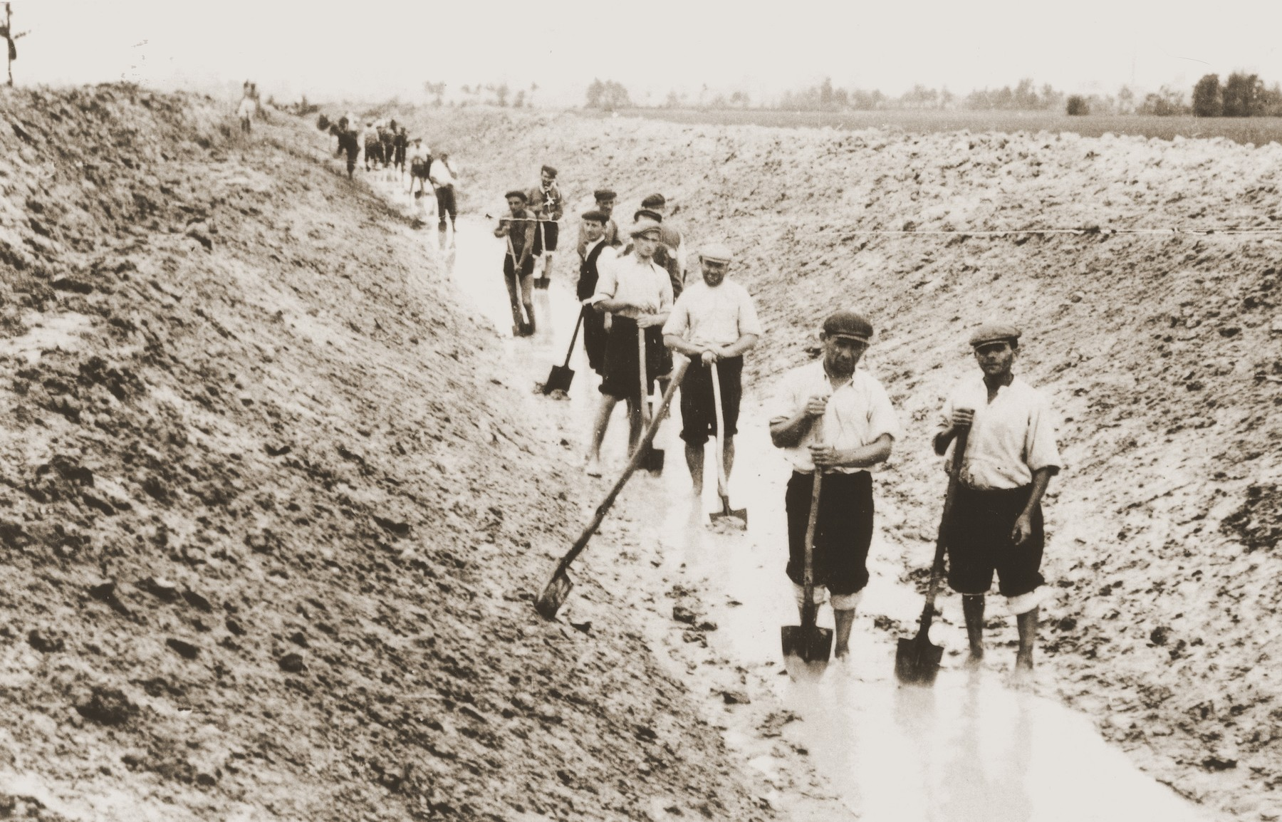 Jews at forced labor stand with shovels in a water-filled trench.