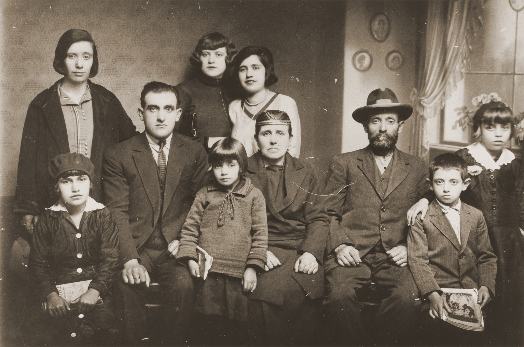 Portrait of the family of Mushon and Rebeka Kamchi in Bitola, Macedonia.  Isak Kamchi is pictured in the front row at the right.