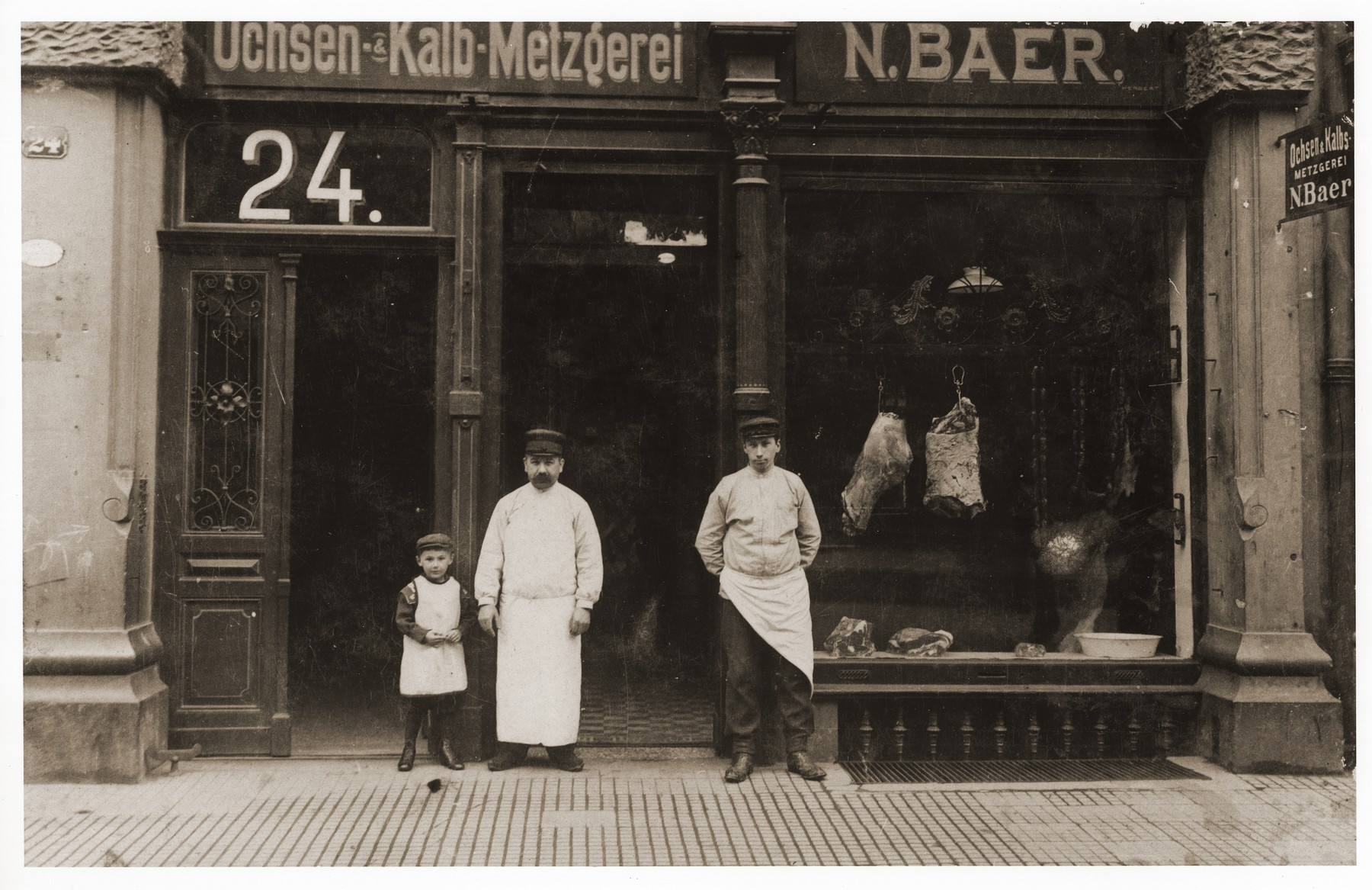 N. Baer (center), the donor's grandfather, poses with members of his family in front of their butcher shop in Frankfurt am Main.