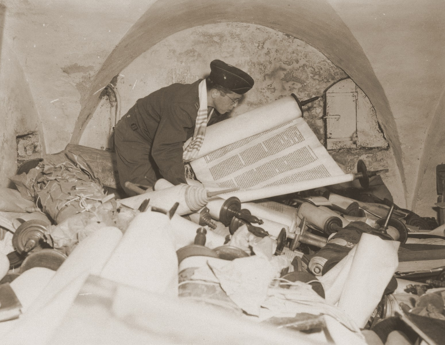 Chaplain Samuel Blinder examines one of the Torah scrolls stolen by the Einsatzstab Rosenberg and stored in the basement of the Institut fuer Juedische Erforschung [Institute for Research into the Jewish Question] in Frankfurt am Main.  The Einsatzstab Rosenberg, established by Reichsleiter Alfred Rosenberg in 1941, travelled to newly occupied countries and confiscated materials from libraries, archives, and private homes.  In this manner, the Institut fuer Juedische Erforschung quickly amassed a library of over 40,000 books.