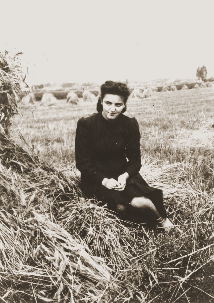 """A young woman sits next to a haystack in the Zelow ghetto.  The Polish inscription on the back of the photo reads, """"To Moniek [Moryc] from Manya as proof of our meeting."""""""
