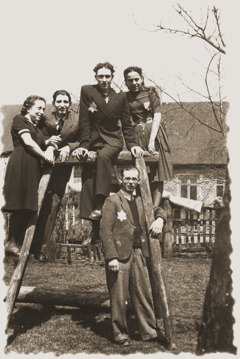 Group portrait of young Jewish men and women posing on a wooden structure in the Zelow ghetto.  Among those pictured is Moryc Brajtbard (second from the left).