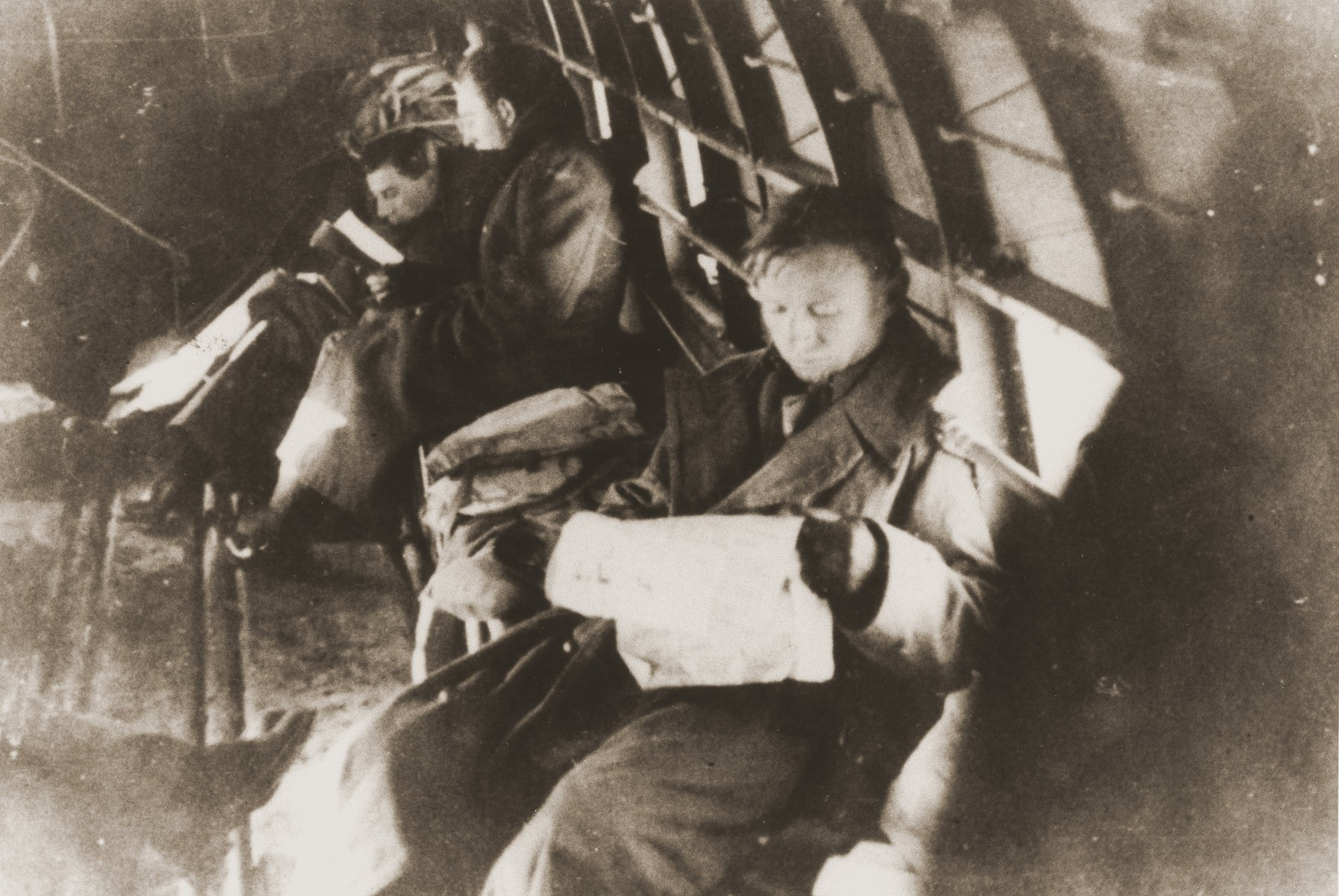 Palestinian Jewish parachutists read on board the airplane before being dropped into Yugoslavia.