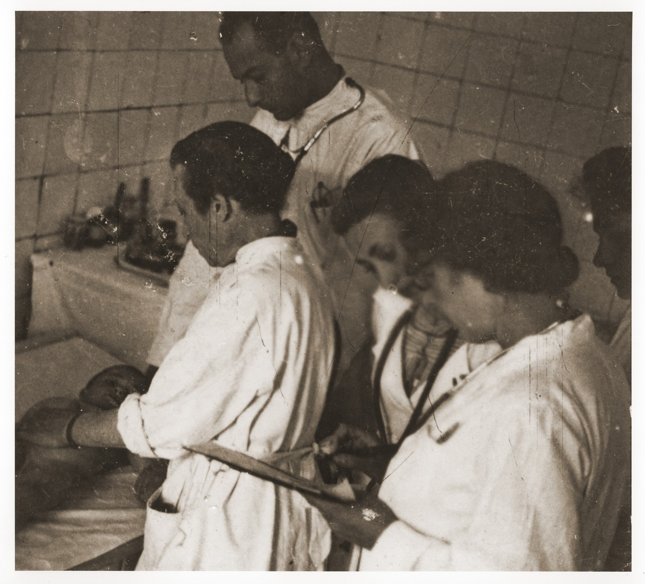 A team of doctors treats an infant in the hospital of the Lodz ghetto.