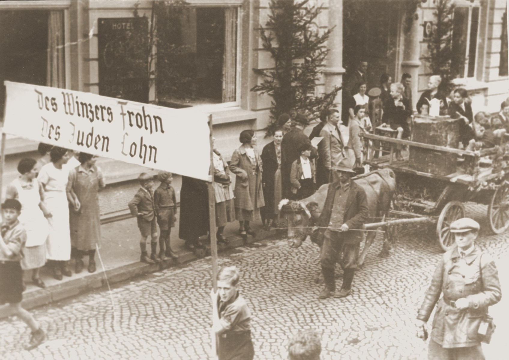 "Residents of Altenar view a Thanksgiving Day parade in which two boys carry an anti-Semitic banner that reads, ""The vintner's happy harvest is the Jew's payday.""  The boys are marching behind an anti-Semitic float depicting a Jew sitting at a counting table, surrounded by enormous bags of money, reveling in his profits from the grape harvest."