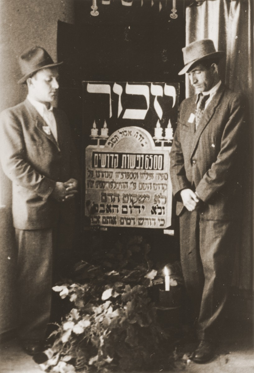 Moryc Brajtbart and his cousin, Leon, stand on either side of a memorial to the 6,500 Jews of Szczercow, who were killed by the Nazis in August, 1942.