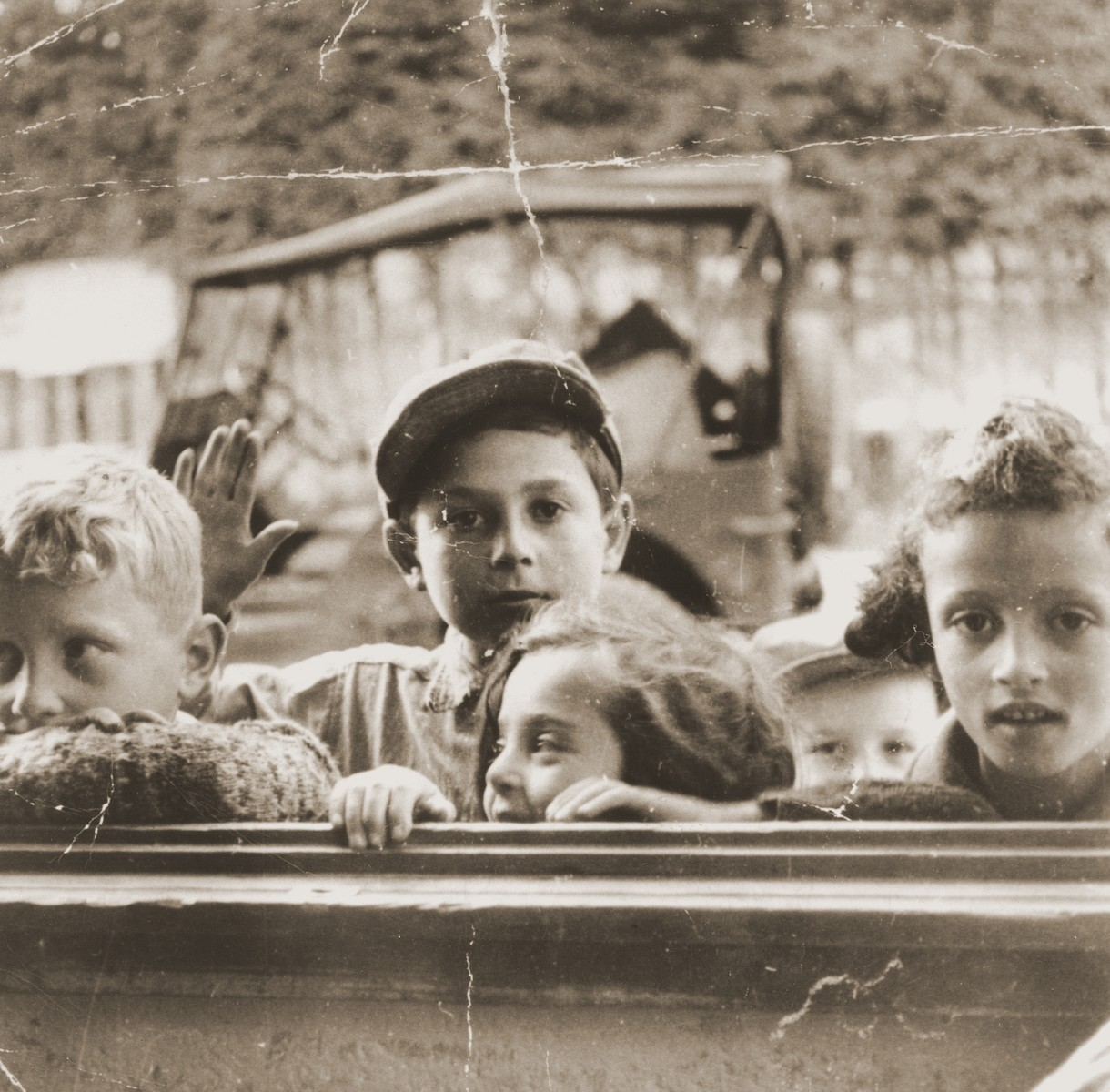 A group of DP children peer in a window at the Feldafing displaced persons camp.