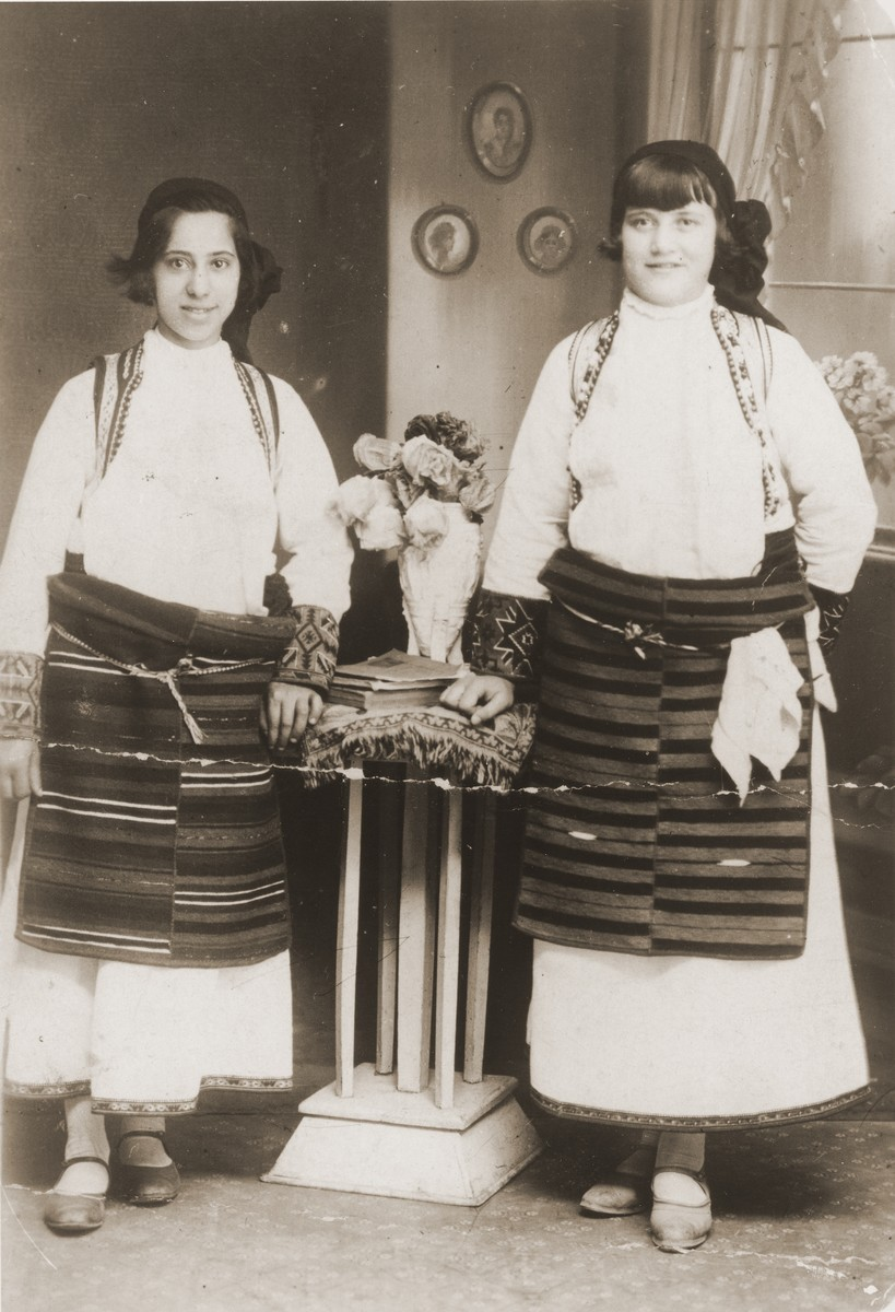 Portrait of two Jewish girls dressed in traditional Macedonian costume in a private home in Bitola, Macedonia.  Pictured are Matilda Kamchi (or Camhi, left) and a friend.  Both perished in Treblinka.