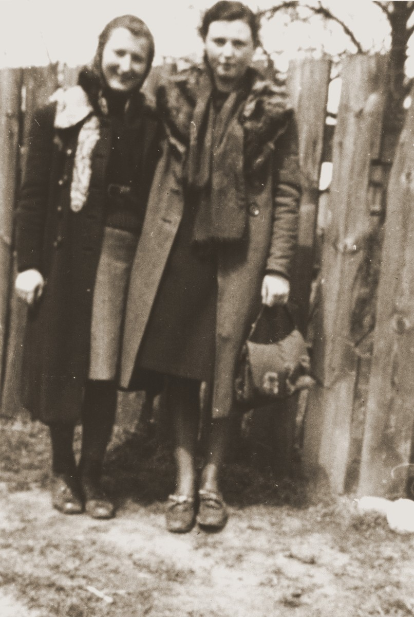 Two young women pose in front of a fence in the Zelow ghetto.