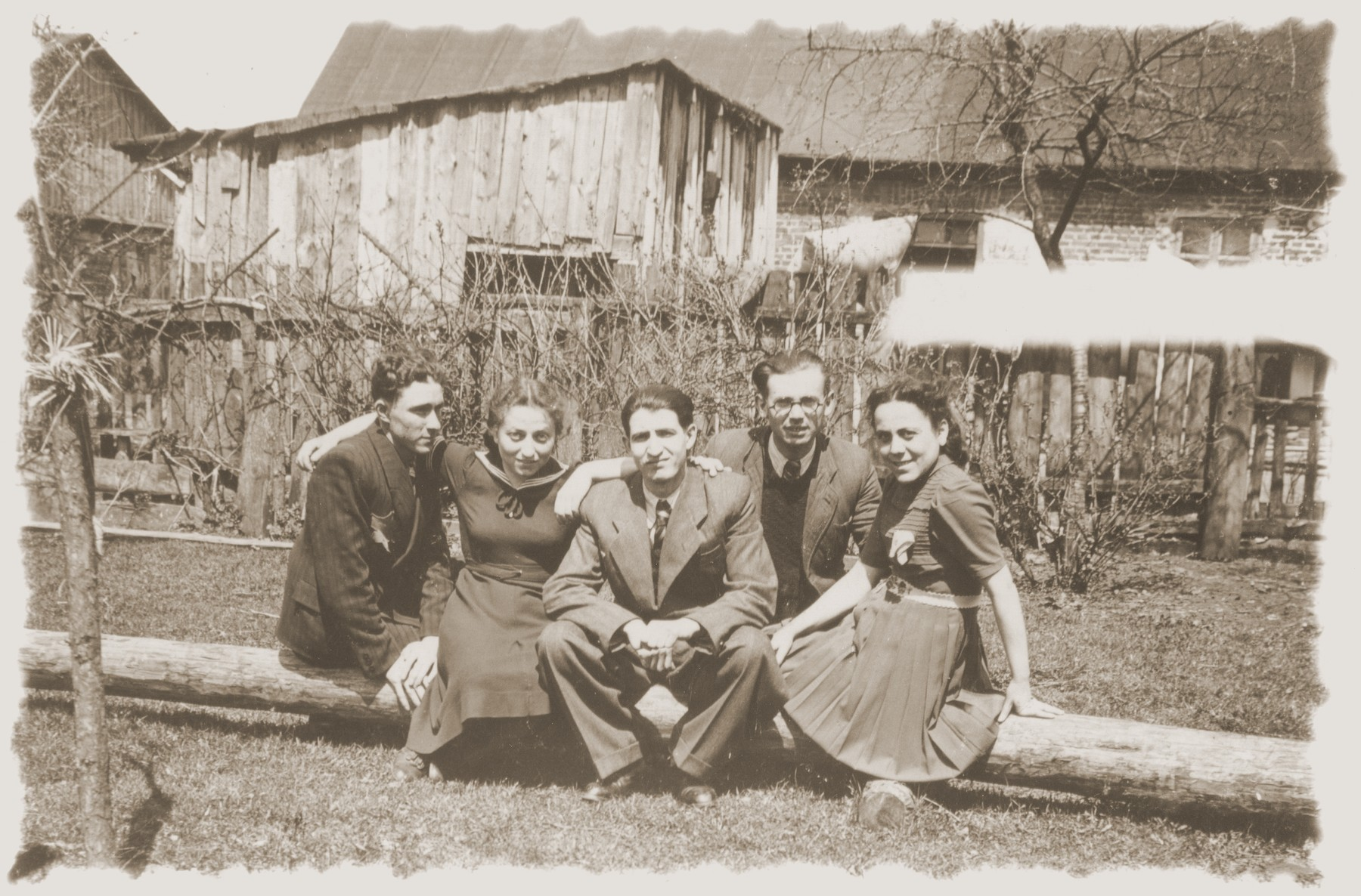 Group portrait of young Jewish men and women seated on a log in the Zelow ghetto.    Among those pictured is Moryc Brajtbart (center).