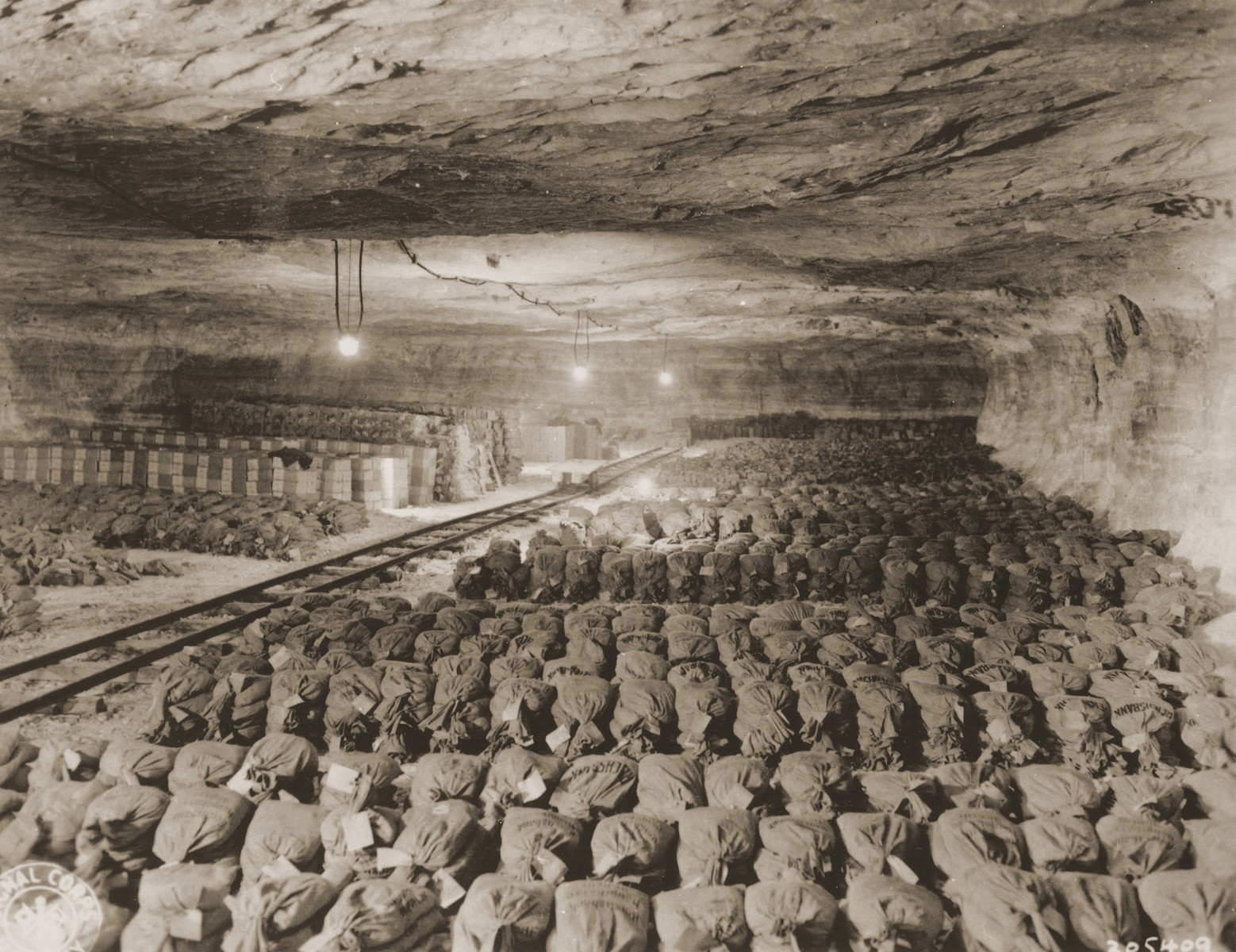 Bundles of currency, confiscated art, and other valuables from Berlin are uncovered by U.S. troops with the 90th Division, U.S. Third Army in the Merkers salt mine.