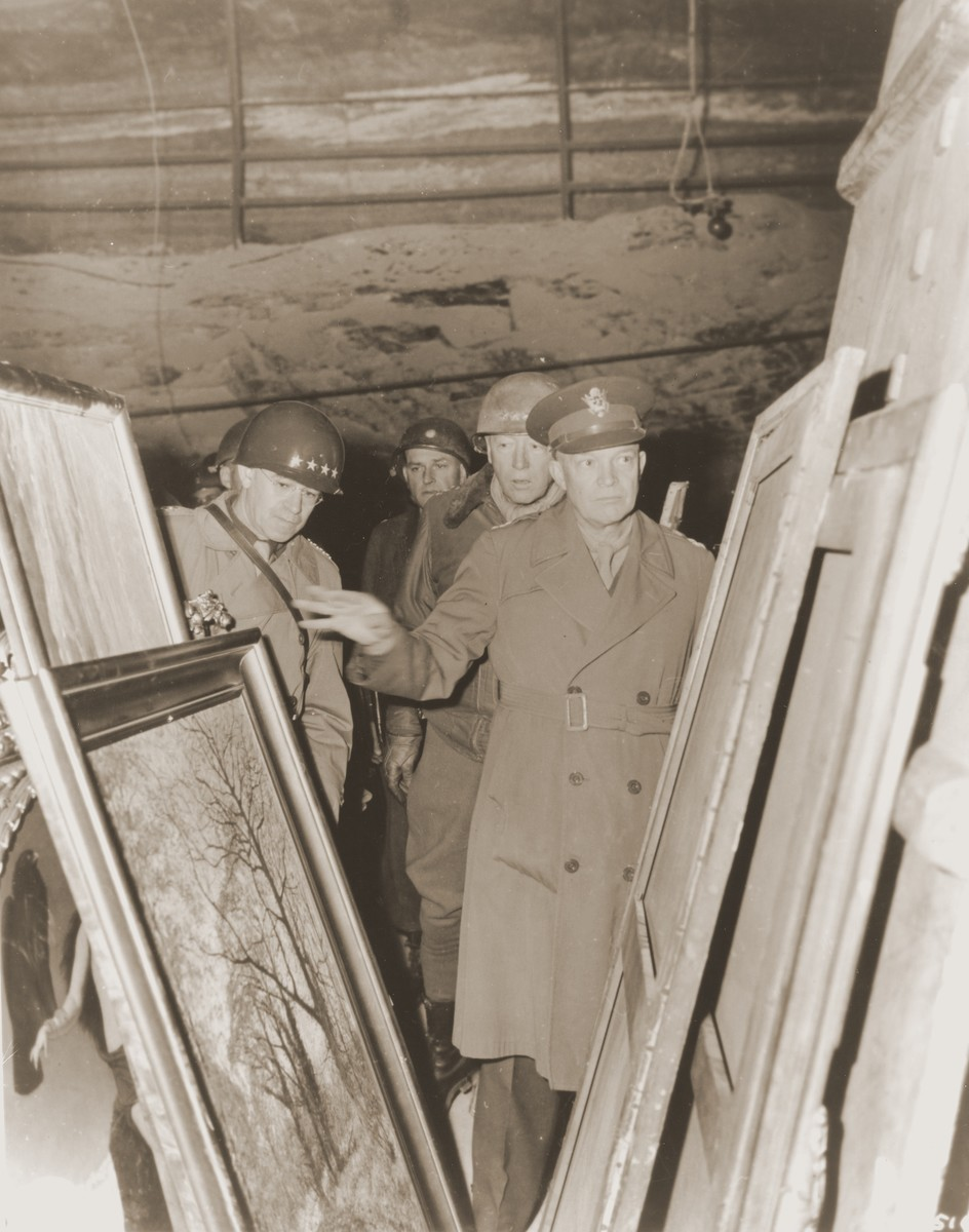 General Dwight D. Eisenhower, Supreme Allied Commander in the West, accompanied by General Omar Bradley (left), and Lt. General George S. Patton, inspect stolen art treasures hidden in the Merkers salt mine.  Also picutred in the center is Major Irving Leonard Moskowitz.