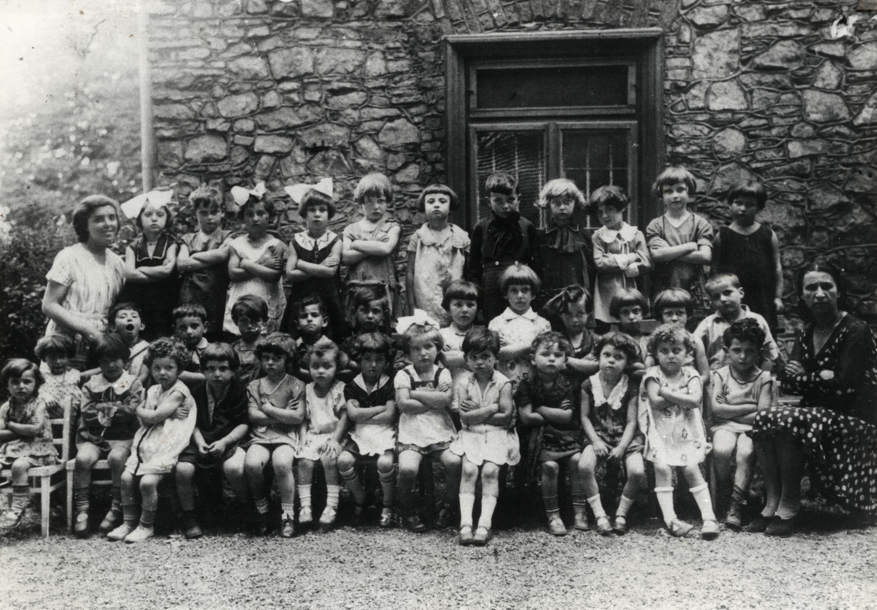 Group portrait of a Jewish kindergarten class in Chrzanow.    Mali is pictured in the middle of the front row with a bow in her hair and crossed arms.  To her immediate left is Lajka Igel (later Karp).