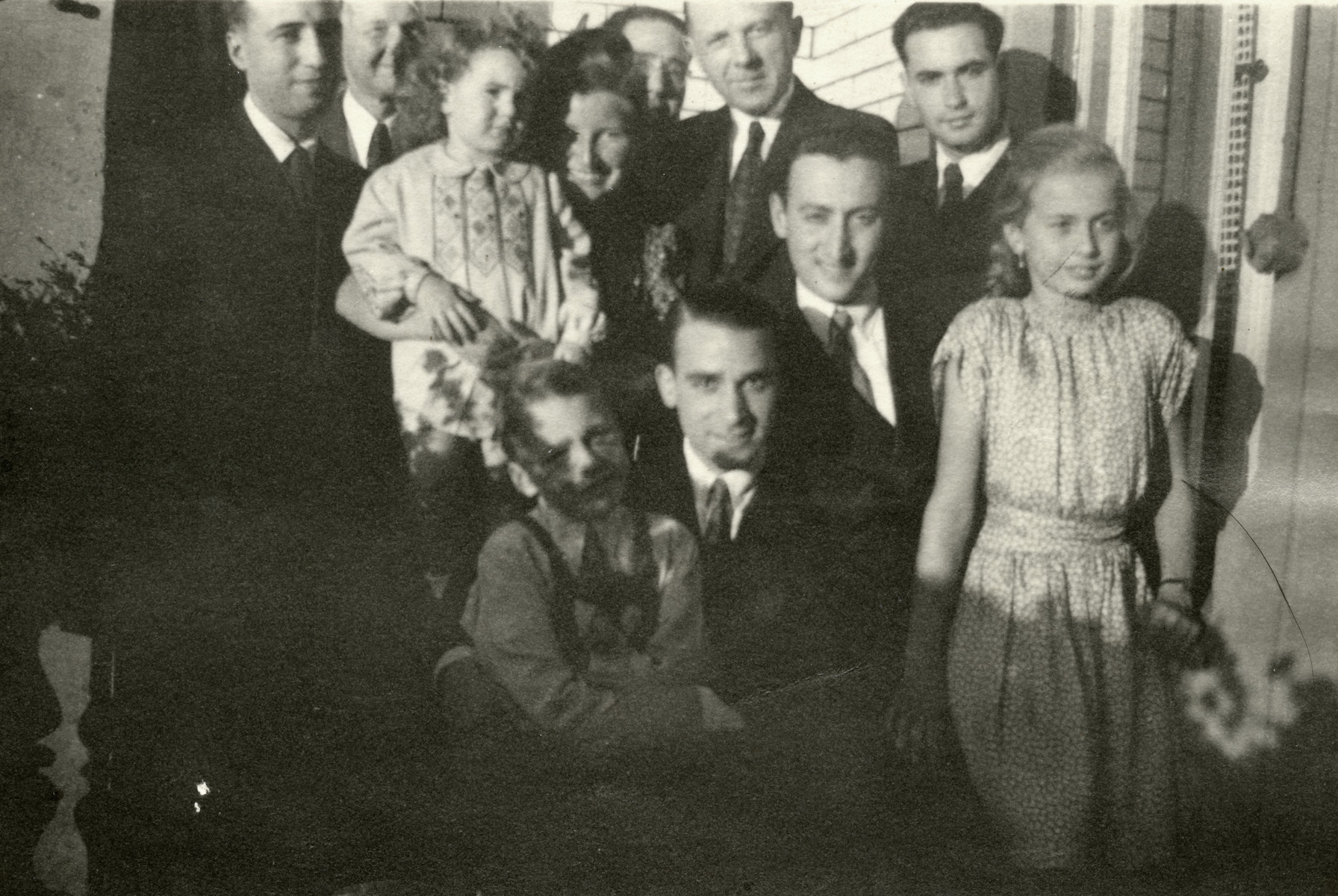 Mali Lamm, a Jew in hiding, poses with her rescuer's daughter and a group of men.  Mali Lam is pictured in back holding young child. Gerda Kreisse is pictured on the right.