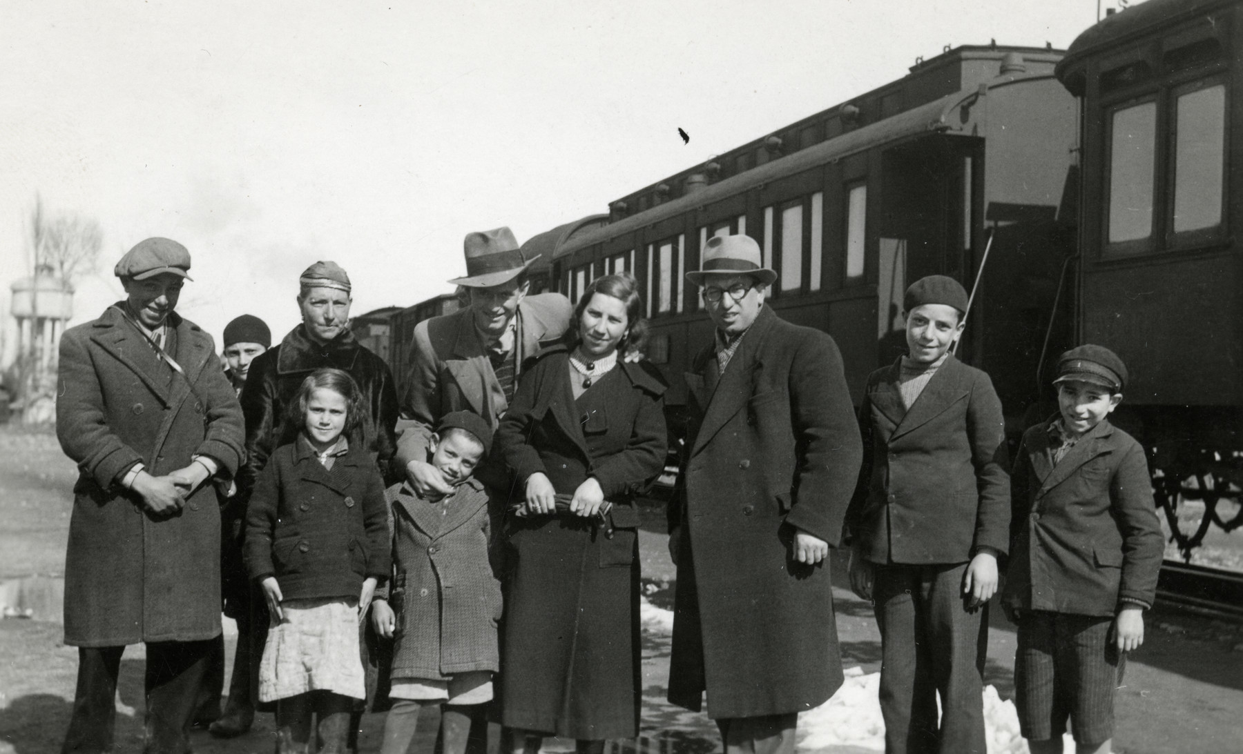 Rabbi Moise Cassorla (father of the donor) poses with his family in front of a train.   Rabbi Cassorla stands third from the right. His mother stands third from the left.