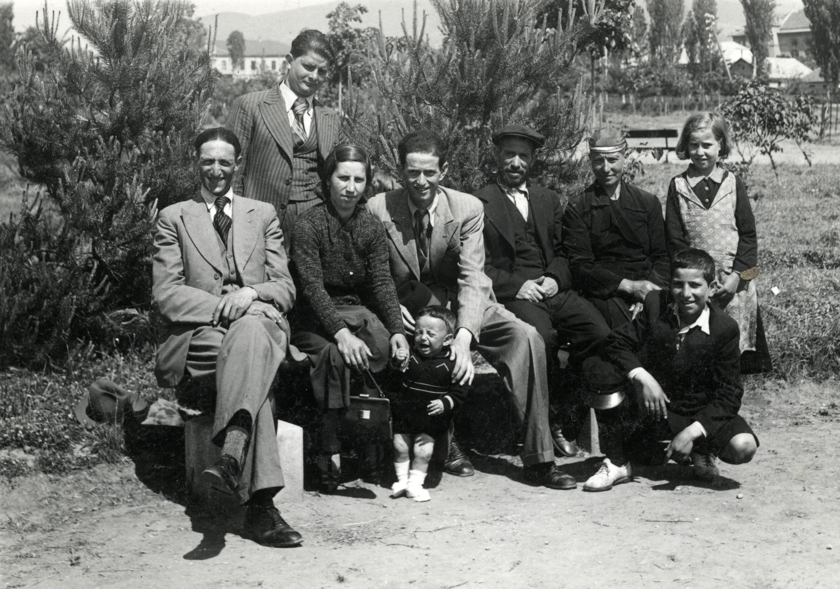 A group of eight people and a baby pose on and around a park bench in Bitola.   The couple sitting on the right of the bench are the parents of Rabbi Moise Cassorla.