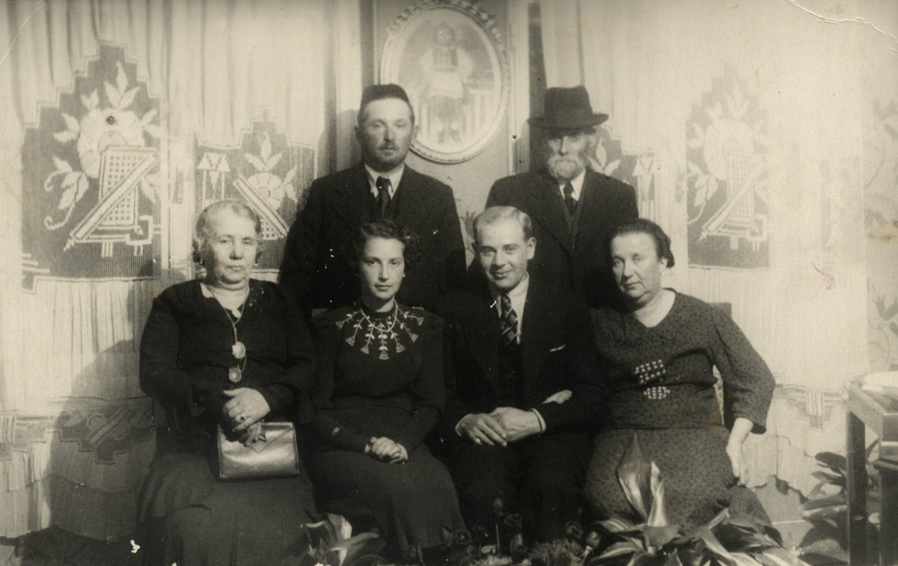 A group of six people poses in a living-room in prewar Krakow.  Among those pictured are Roman Berger and his wife (great-grandparents of the donor).
