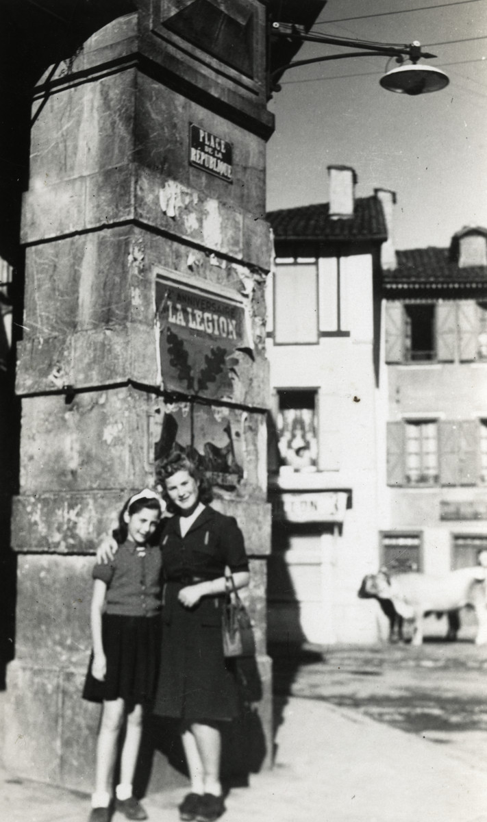 "Malvine and Rachelle Reicher (aunts of the donor) pose on a street under an archway in wartime France in a village where they were sent by the local Red Cross..   Above them are a poster that reads ""La Legion"" and a ""Place de la Republique"" street sign."