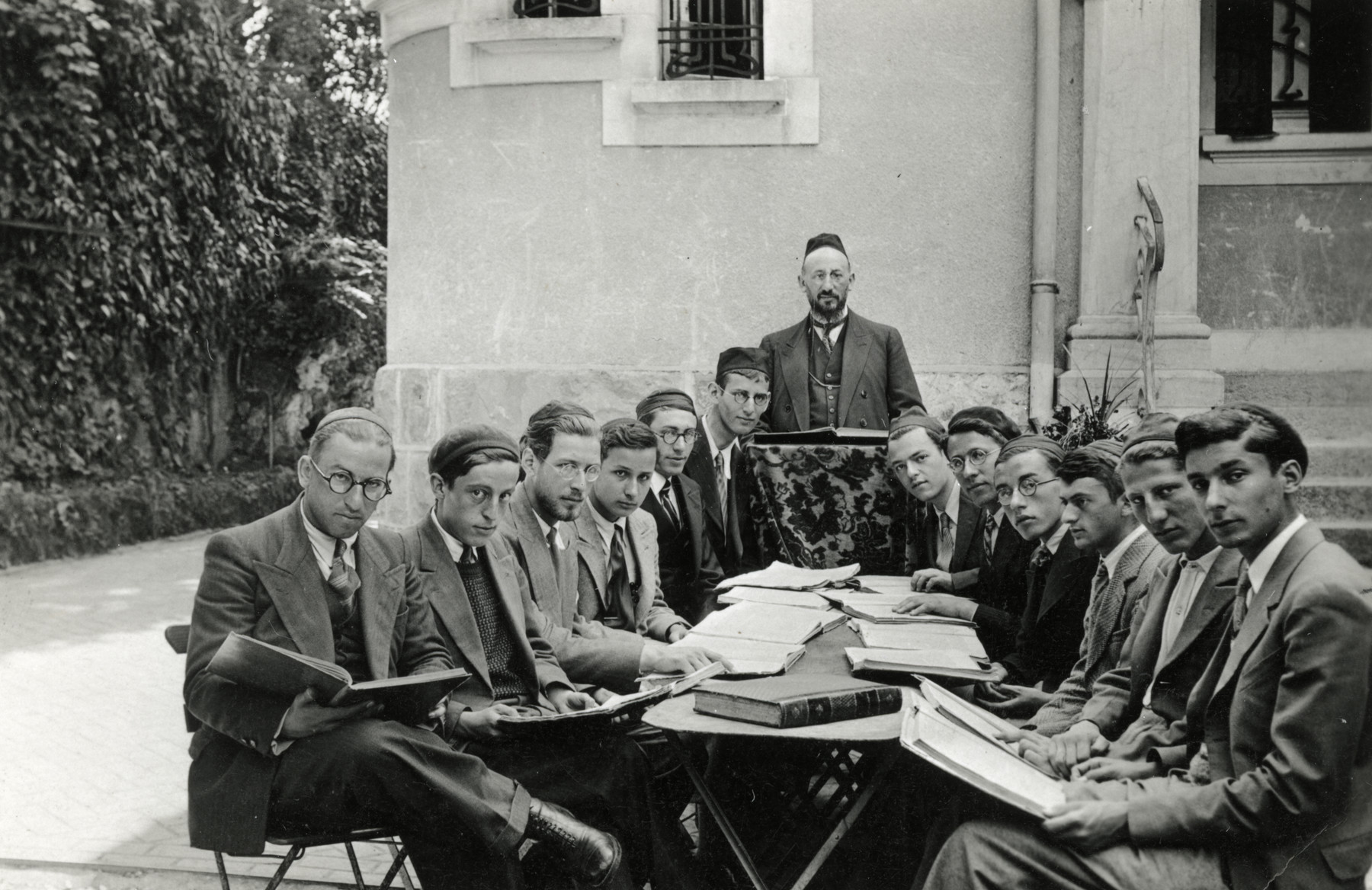 A group of rabbinical students studies outdoors around a table.  The teacher is standing at the far end of the table. Moise Cassorla (father of the donor) is sitting at the front left.