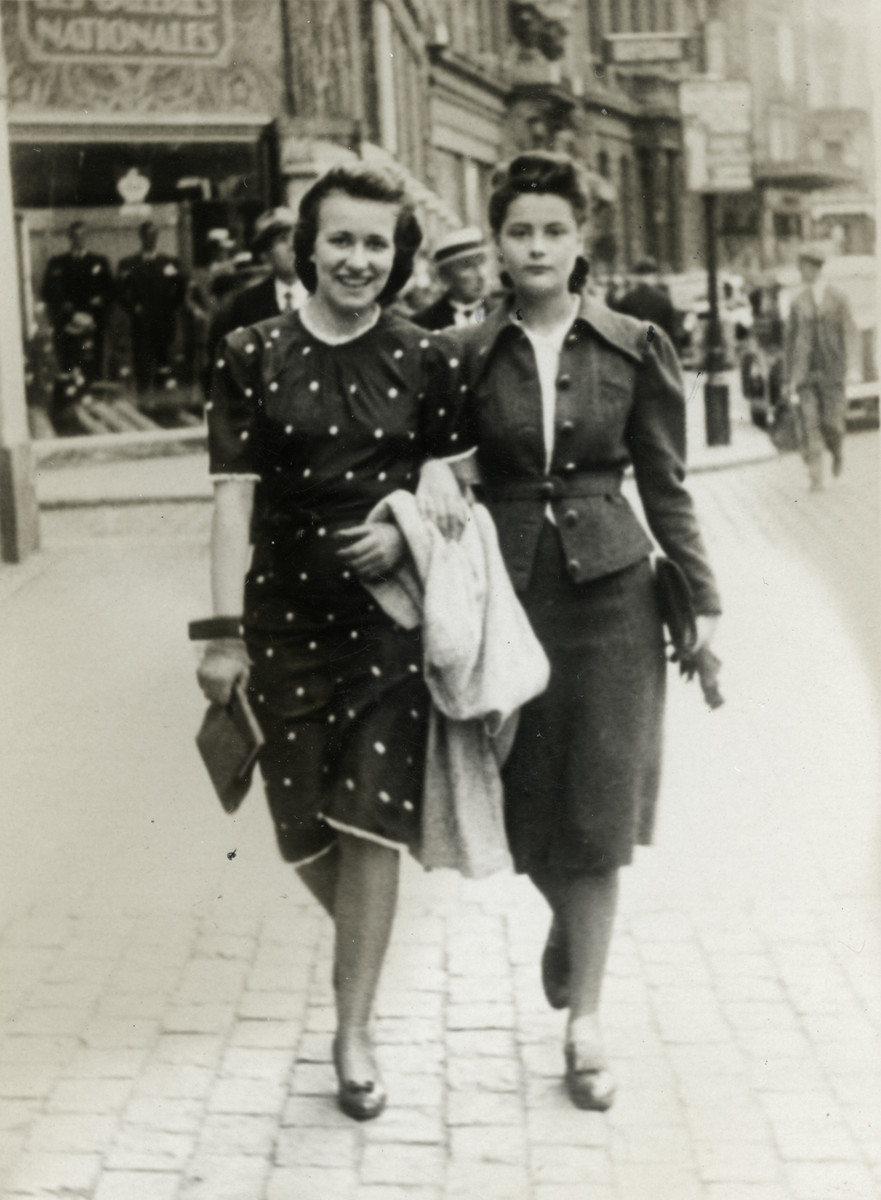 Fanny Reicher walks down a street of Antwerp holding the arm of another woman.
