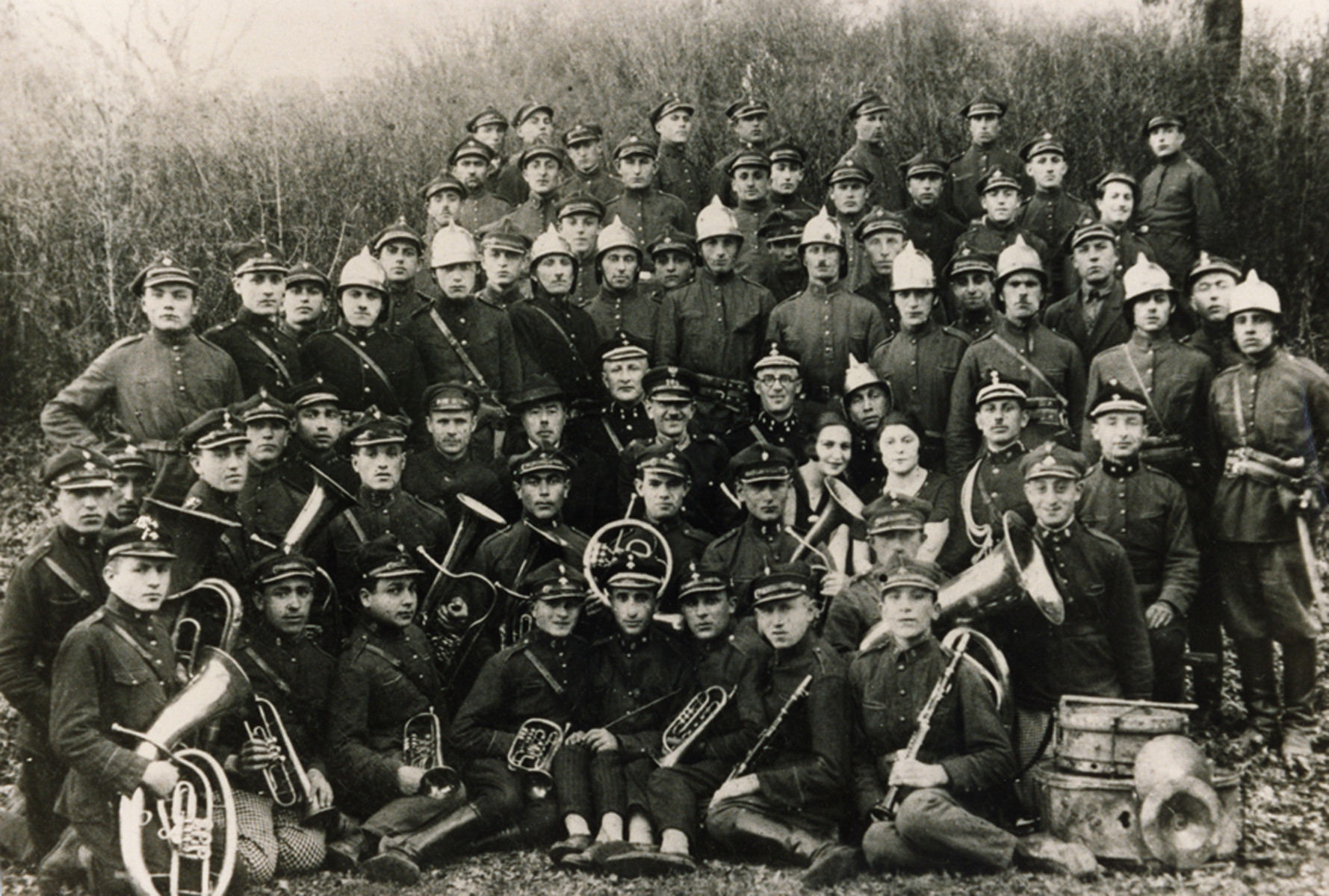 Group portrait of members of the Nowogrodek fire brigade, many are holding musical instruments.