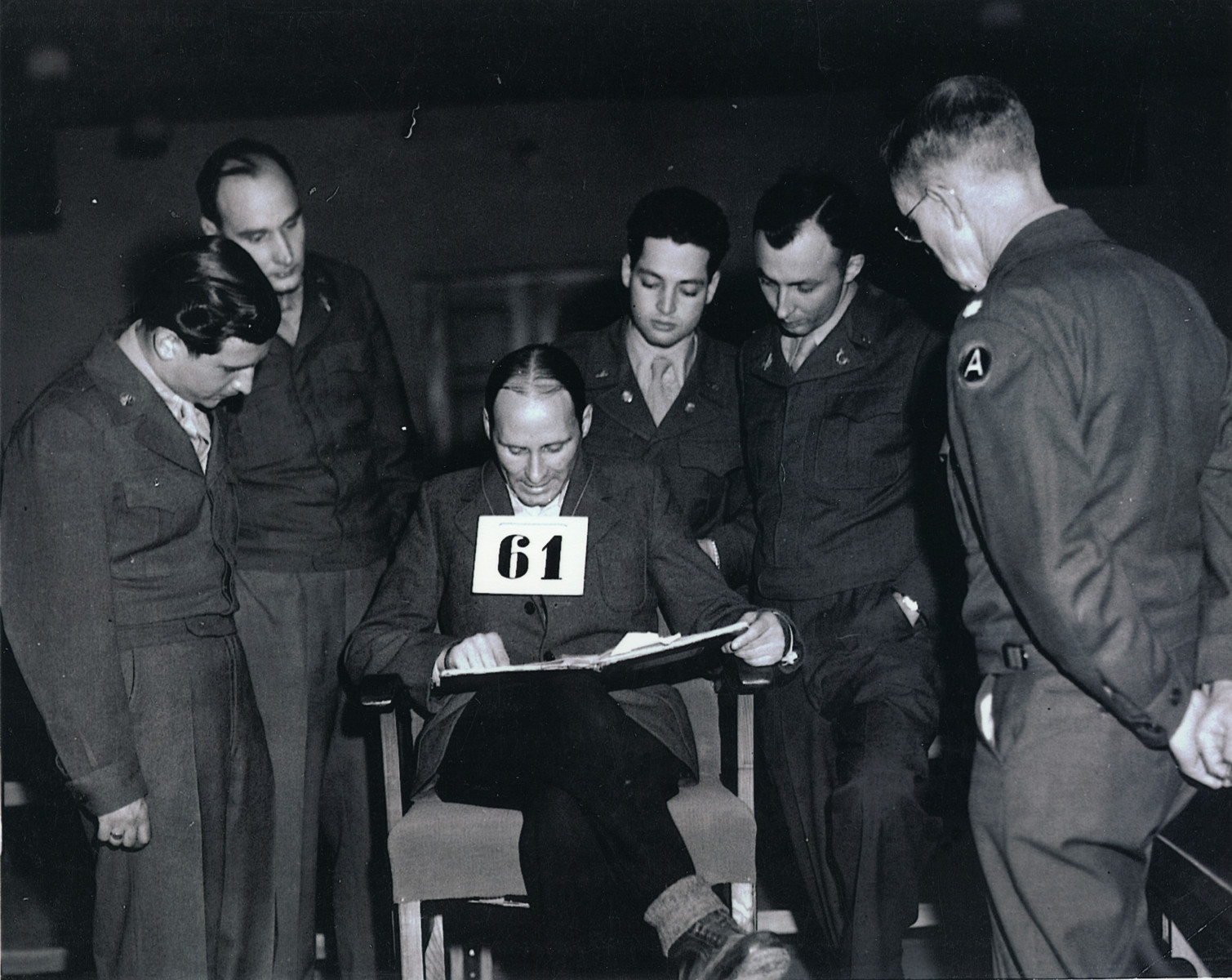 Victor Zoller (defendant 61) examines documents during the Mauthausen war crimes trial.  From left to right are the interpretter, Lt. Col. Ernst Oeding (defense attorney), Victor Zoller, Lt. Paul Guth (interrogator), William Denson (chief prosecutor) and Lt. Robert Wilson.  Victor Zoller former commander of the SS-Totenkopf guard battalion was sentenced to death by hanging.