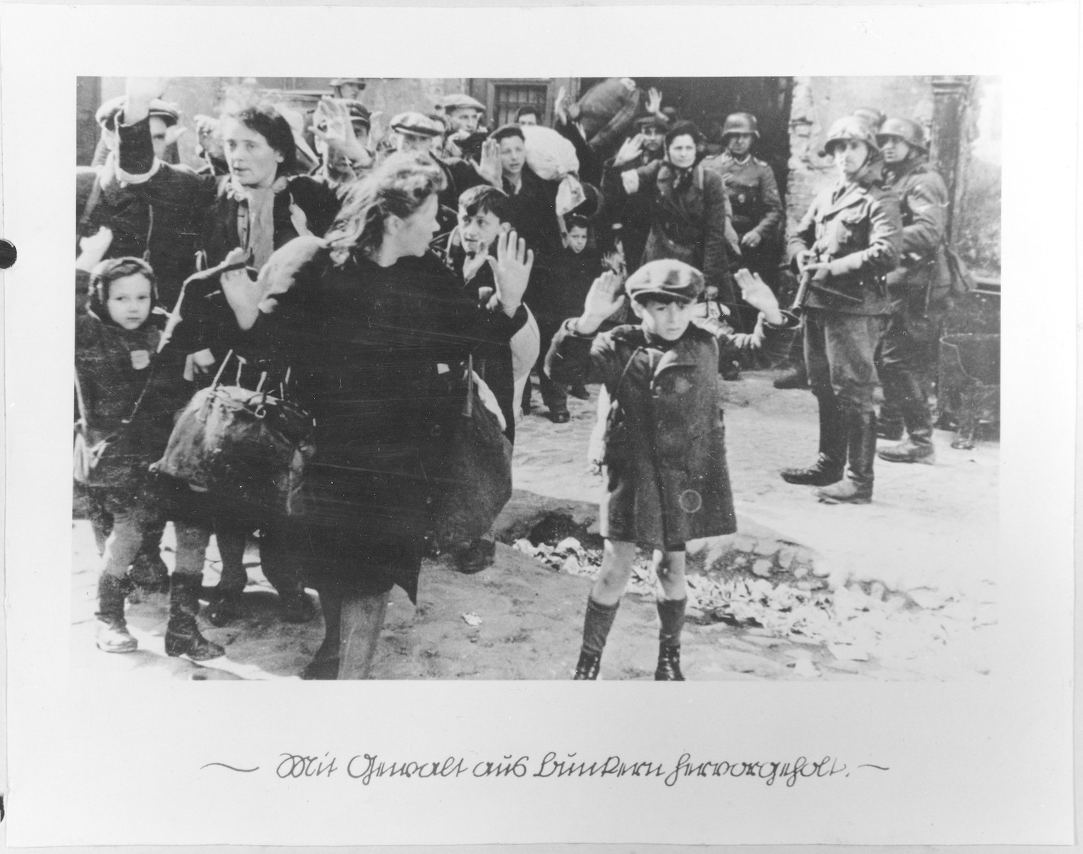 "Jews captured by SS and SD troops during the suppression of the Warsaw ghetto uprising are forced to leave their shelter and march to the Umschlagplatz for deportation.    The original German caption reads: ""Pulled from the bunkers by force.""  The SD trooper pictured second from the right, is SS-Rottenfuehrer Josef Bloesche, who was identified by authorities using this photograph.  Bloesche was tried for war crimes by an East German court in 1969, sentenced to death and executed in July of that year.    The little girl on the left has been identified as Hanka Lamet, who is standing next to her mother, Matylda Lamet Goldfinger (the woman second from the left).  The boy carrying the sack has been identified as Leo Kartuzinsky and the woman in the front has been identified as Chana Zeilinwarger.  Numerous people have identified the boy in the foreground as either Arthur Domb Semiontek, Issrael Rondel, Tsvi Nussbaum or Levi Zeilinwarger, but none of these identifications can be conclusively corroborated"