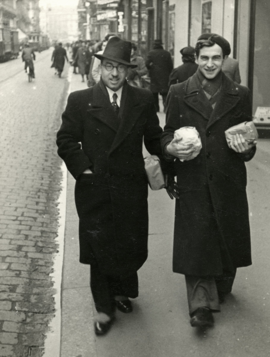 """Rabbi Moise Cassorla and a man walk down a street of Toulouse carrying paper-wrapped packages.   Caption in the back says """"Toulouse Pourim 1941""""."""