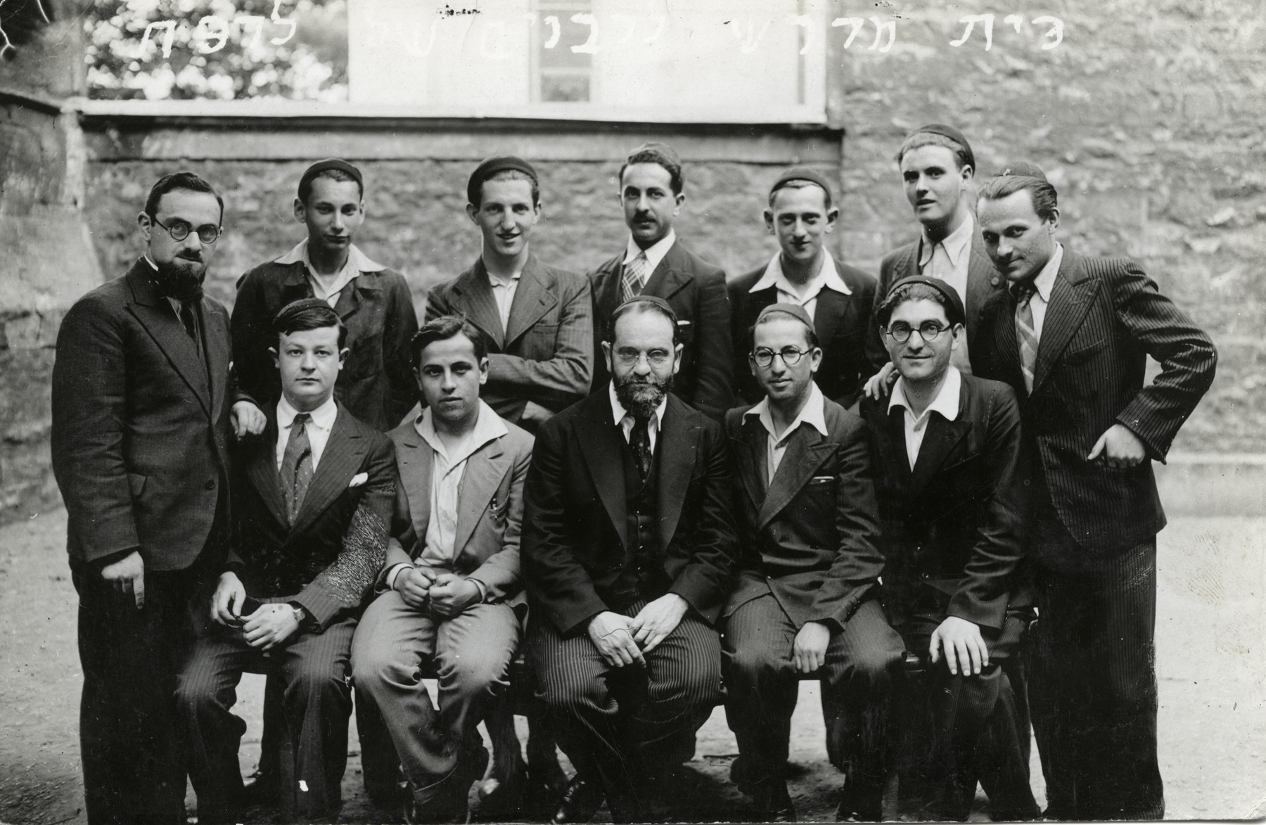 Jewish rabbinical students pose in front of a building.   Moise Cassorla, father of the donor, is sitting on the bench, second person from the right. Rabbi Joseph M Brandriss is pictured seated on the left.    Rabbi Brandriss received his ordination from the Consistoire in 1939 and served as a Jewish Chaplain in the 107th Infantry of the French Army.  He spent the war years in a prisoner-of-war camp in Germany. After the war he was appointed Rabbi in St. Amiens and Grand-Rabbin du la Nord de la France at Lille prior to immigrating to the United States.