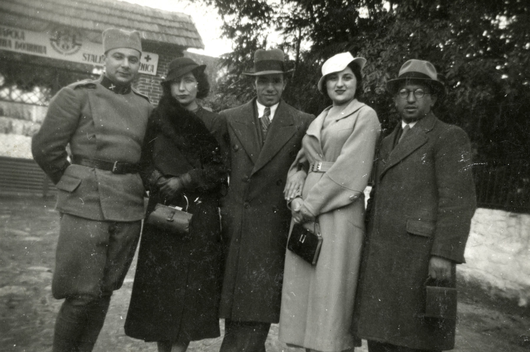 """A group of Macedonian Jews poses in front of a hospital.  Pictured are Rabbi Cassorla (father of the donor, on right), his sister, a couple and a man in a uniform (who may be """" Joseph Pappo"""", a Serbian friend)"""