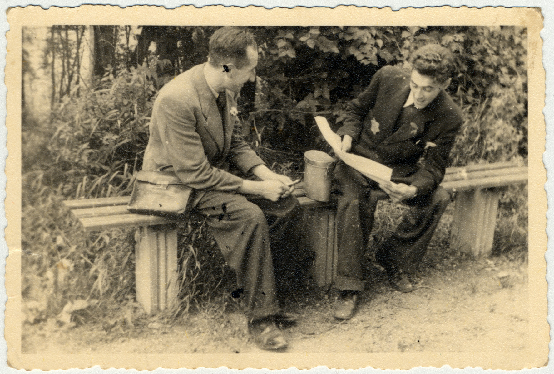 Two young men are sit on a bench in the Lodz ghetto.   On the right is Arie Princ (later Ben Menachem).
