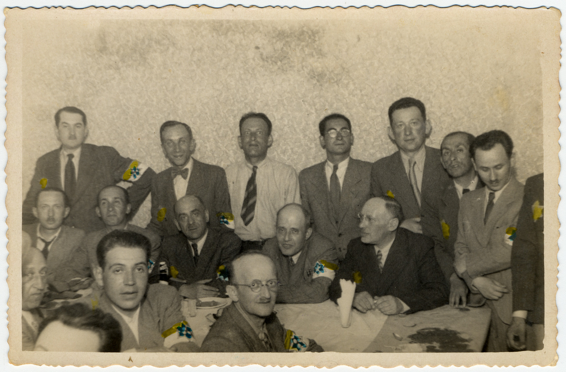 Partially colorized photograph of members of the Lodz ghetto administration, including the heads of workshops, police and members of the Sonderkommando, at a social gathering.  Among those pictured are: donor's maternal uncle Leon Fajtlowicz, in charge of the leather workshops (standing fourth from the left), Zygmunt Reingold, director of food supply (standing fifth from the left), Baruch Praszker, chief of special assignments (standing second from the right),  Leon Rozenblatt, chief of the ghetto police (seated on the far side of the table, third from left) and David Warszawski, director of the tailoring workshops (seated on the far side of the table, first from right).
