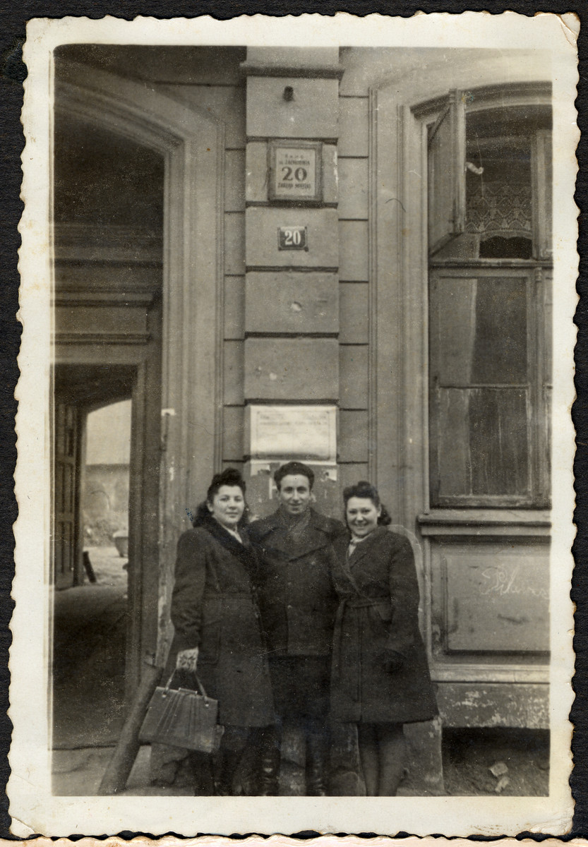 "Group portrait of Jewish survivors posing in front of the ""kibbutz"" on 20 Zachodnia Street in Lodz.   Pictured from the left are Renia Klugman [?], Lolek Grynfeld and Rachel Grynglas."