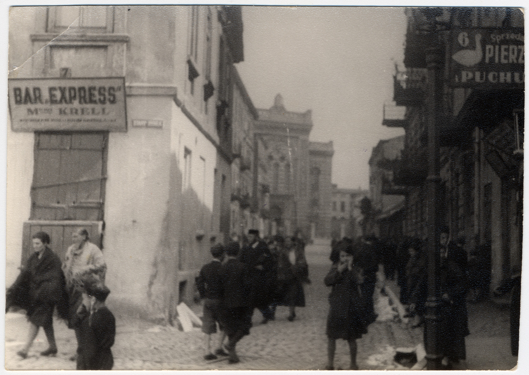"""View of a commercial street in Lodz.    On the left is the bar """"Express"""" which belonged to the donor's grandfather, Michuel Krell, and in the background is the Alteschule [Old Town Synagogue]."""