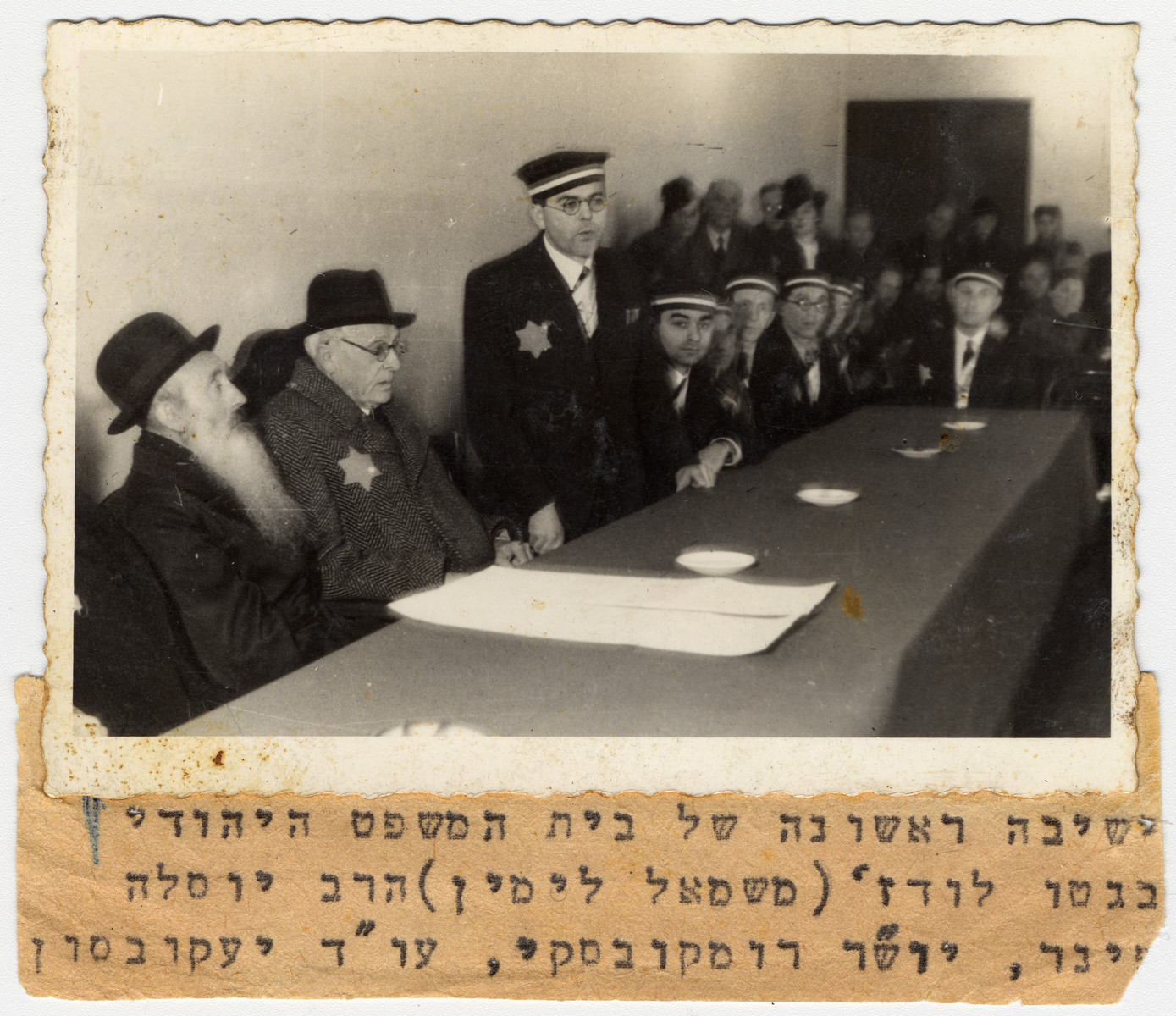 Mordechai Chaim Rumkowski, chairman of the Jewish Council in the Lodz ghetto, attends the swearing-in ceremony for the judges of the Jewish court.  Speaking is attorney Stanislaw Jakobson.  Pictured on the right of Rumkowski is Rabbi Yosif Fajner.