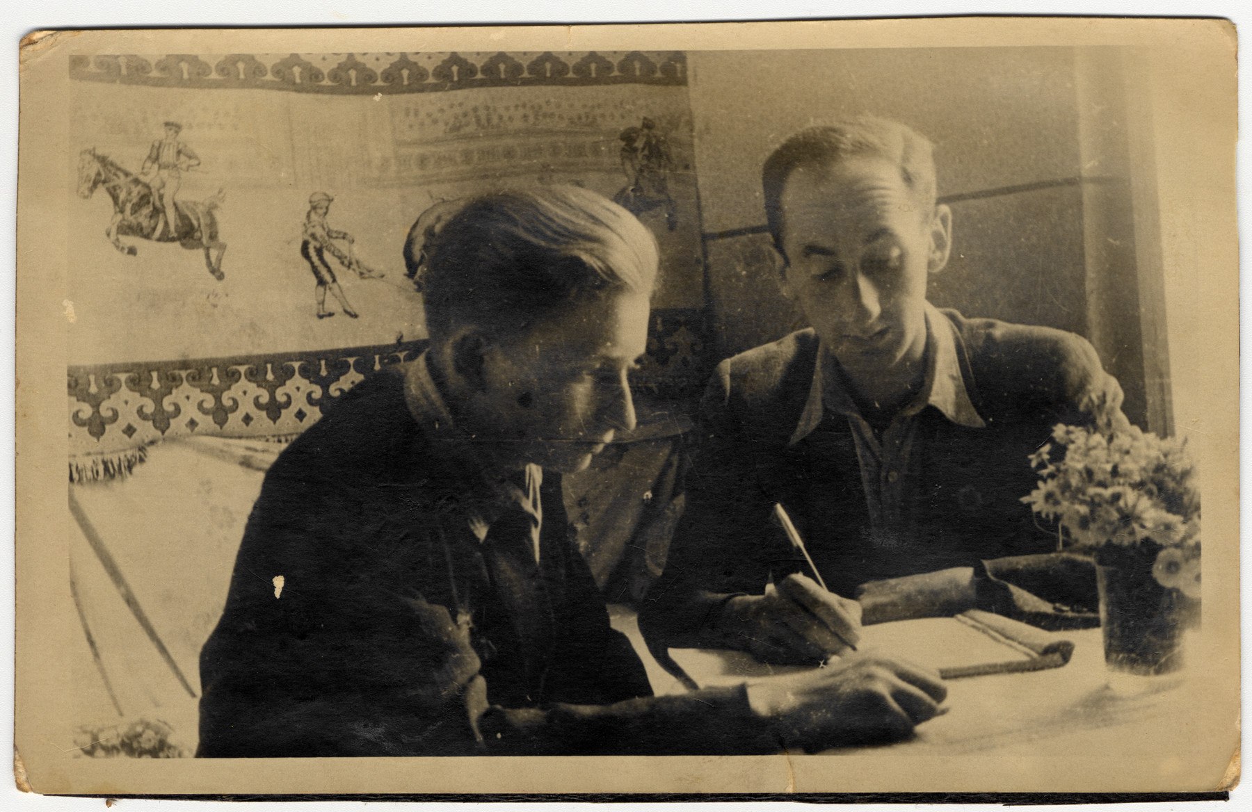 Two young men work at a desk [in the Lodz ghetto].  On the left is Abram Zelig and on the right is Aron Jakubson.