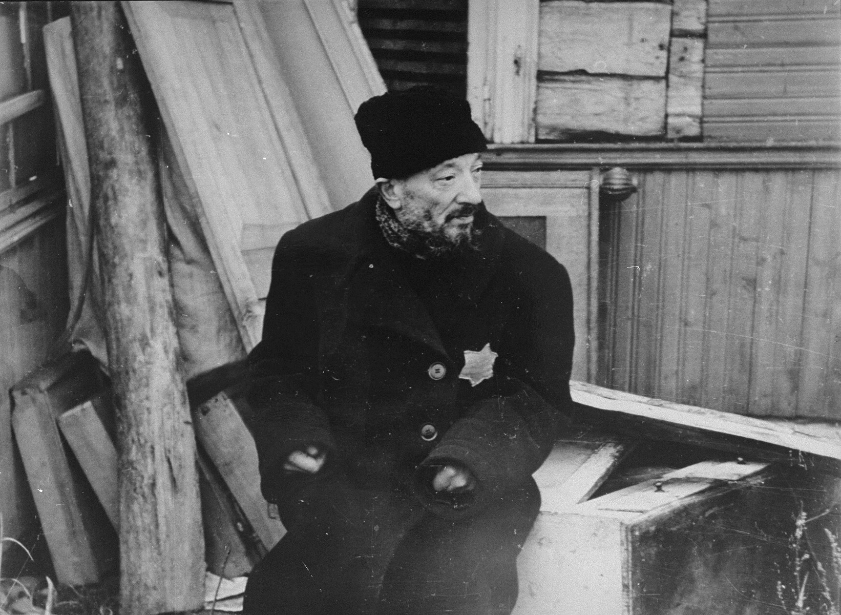 The preacher, Rabbi Most, sits outside his dwelling in the Kovno ghetto, where he awaits deportation.