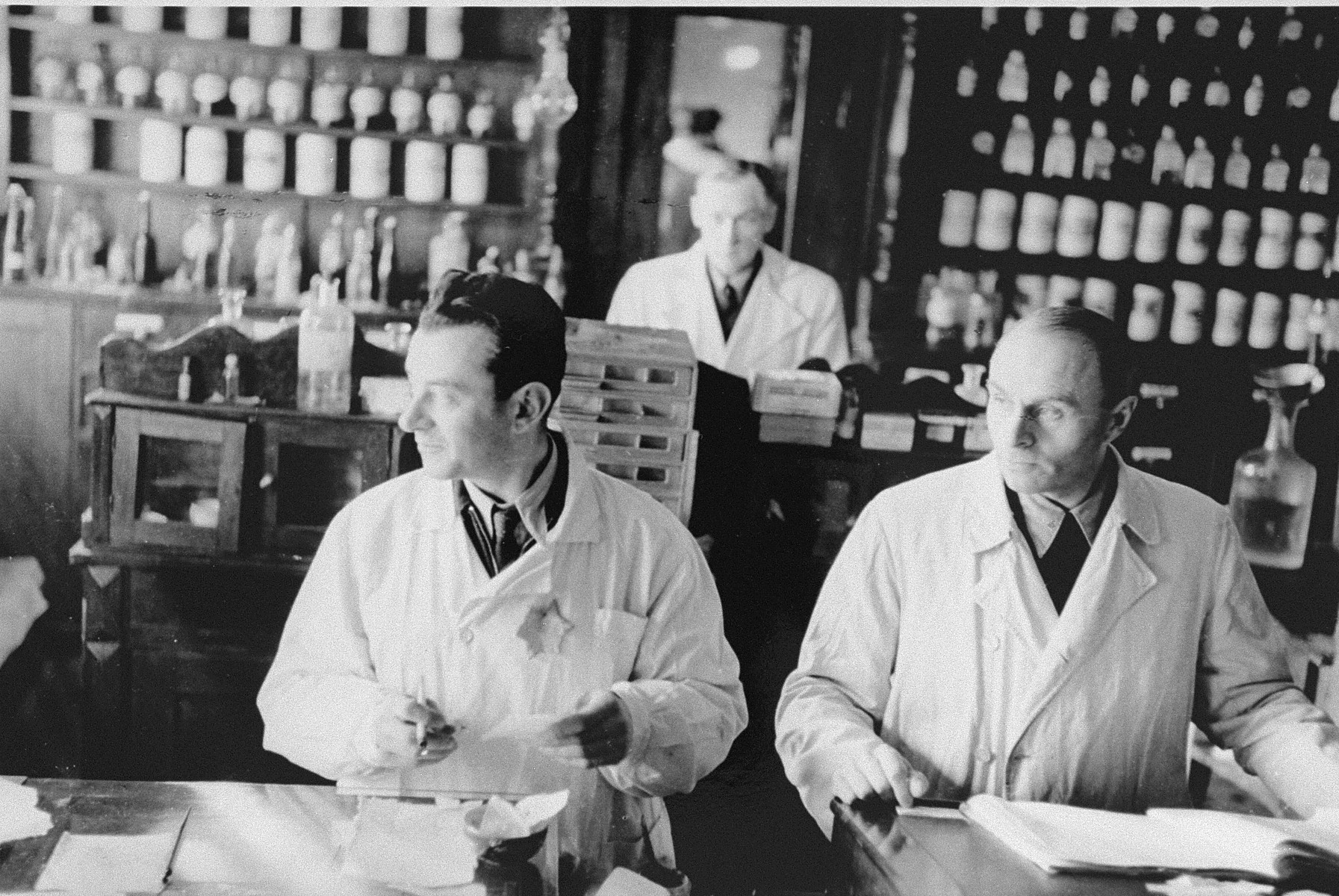 Jewish pharmacists at work in the only pharmacy in the Kovno ghetto.   Among those pictured are head pharmacist Aizik Srebnitzki (left), and N. Segalsohn (from Memel).  Aizik Srebnitzki, who was active in the ghetto's Zionist underground, kept a clandestine radio in the basement of the pharmacy for use by the underground.