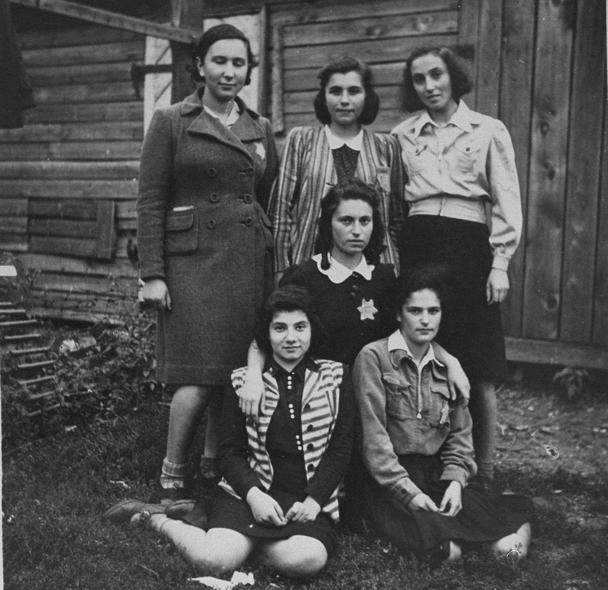 Group portrait of six young women in the Kovno ghetto who are members of the Irgun Brit Zion Zionist youth movement.  Pictured in the back row (left to right) are:  Bela Gurewitz (now Rosenberg), Tania (Yonina) Zaks,  Doli Simon; in the middle, Nechama Boruchson (now Kaufman); front row, left: Lala Finkelstein; right, Rosa Simon (now Shoshana Axelrad).