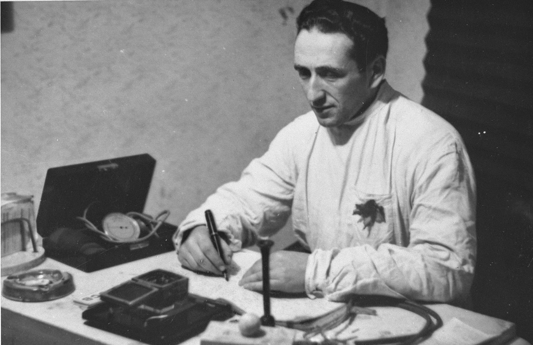 Dr. David Arolianski works at his desk in his clinic in the Kovno ghetto.    Dr. Aroliansky was killed in a bunker during the ghetto's liquidation, June 1944.