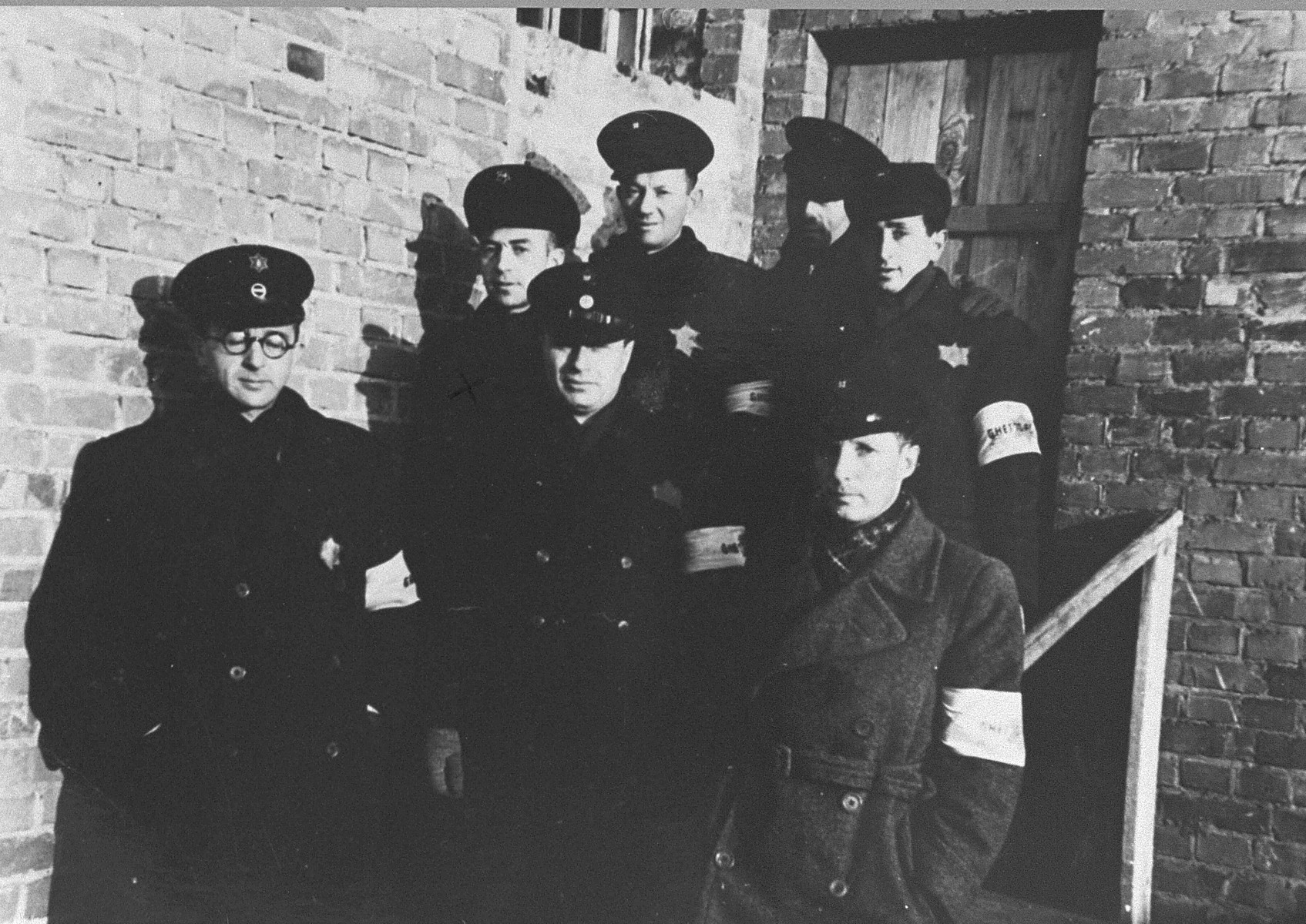 A group of Jewish police poses in front of the ghetto prison.  From left, first row: Kalberski (deputy chief), Melamdowicz (chief), Nikko Lewinstein. Back row, from left: Mordechai Kronowski, Elchanan Rosental, Jaffe, Yehuda Sergey.  There were two prisons in the Kovno ghetto, one for people caught at avoiding forced labor and the other for criminals. This photo was taken in front of the criminal prison. These policemen served as prison guards.
