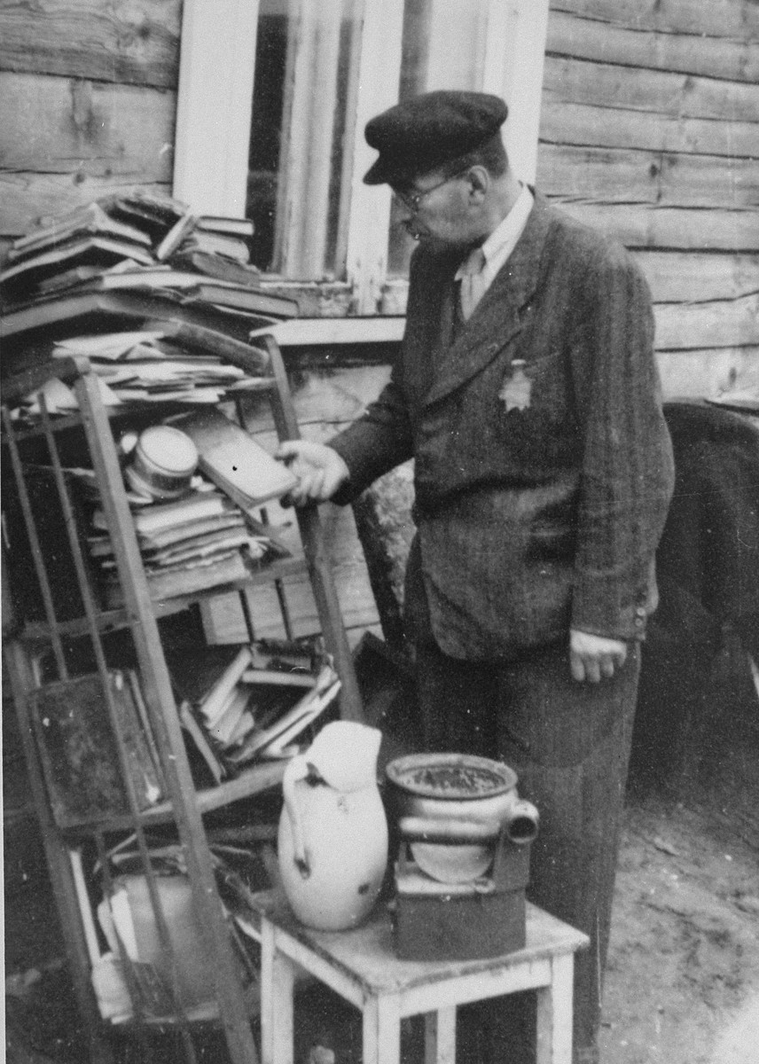 A Jew looks through discarded books piled outside a house in the Kovno ghetto.