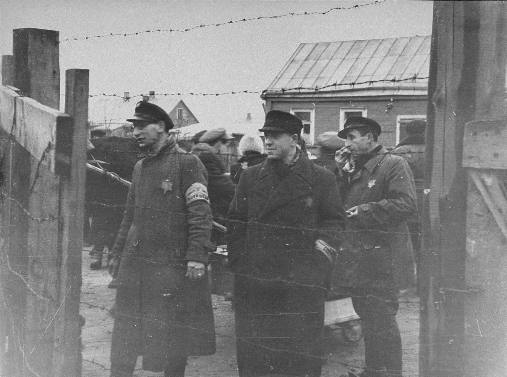 Three Jewish ghetto officials stand at one of the gates to the Kovno ghetto.   Pictured are Pavel Margolis (center), head of recruitment at the Jewish labor office in the ghetto, Yankel Kaplan (far right), a member of the ghetto fire brigade  .